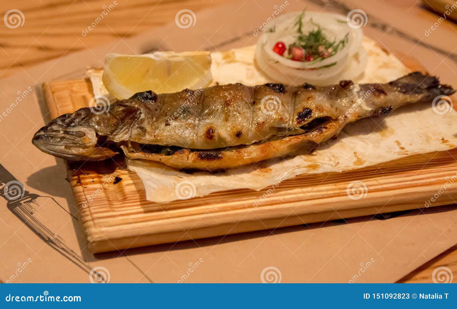 Πέστροφα ψαριών για το γεύμα, σε ένα ξύλινο πιάτο