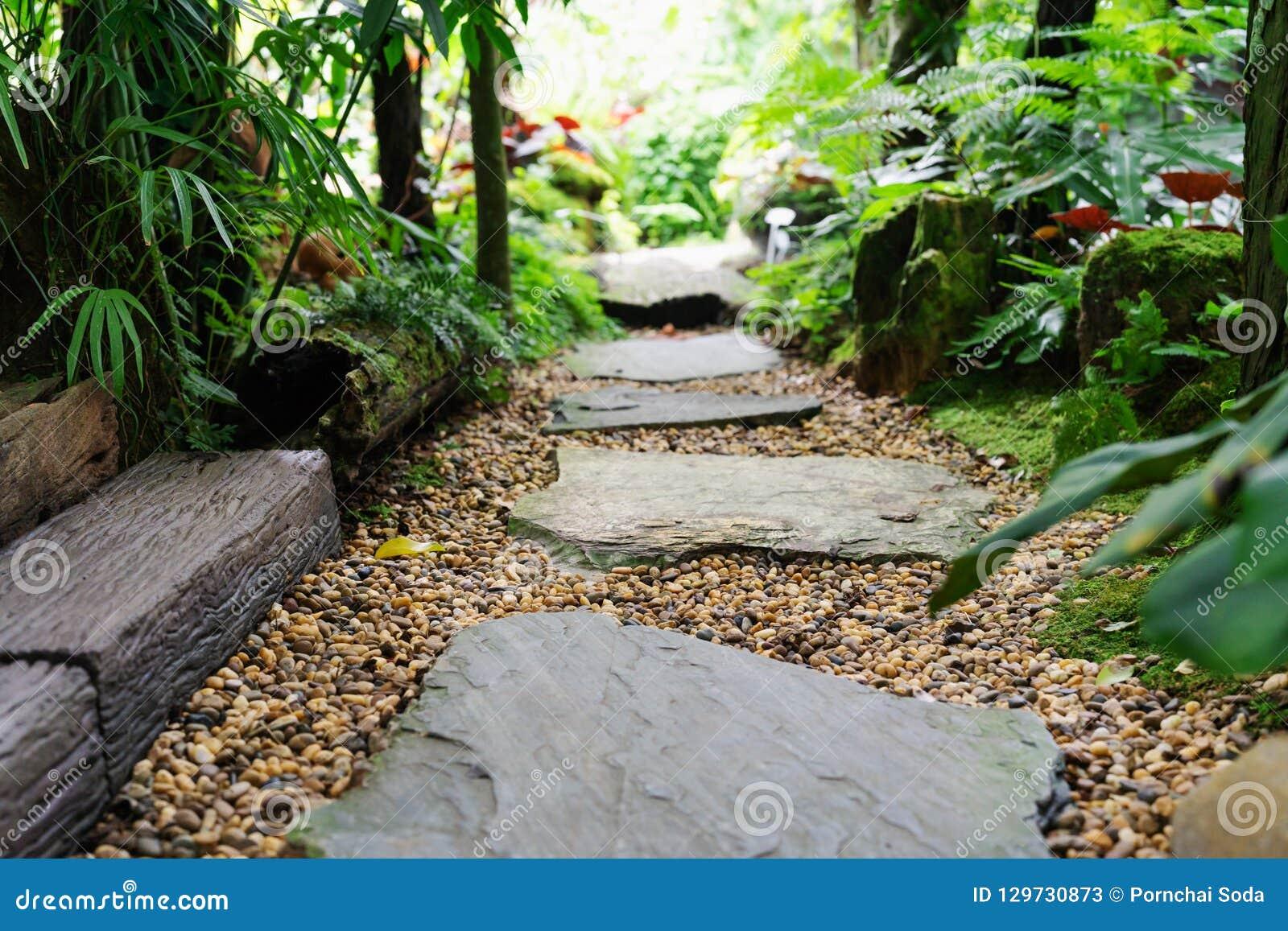 Πέτρινη διάβαση πεζών στην πέτρα βημάτων κήπων στο αμμοχάλικο