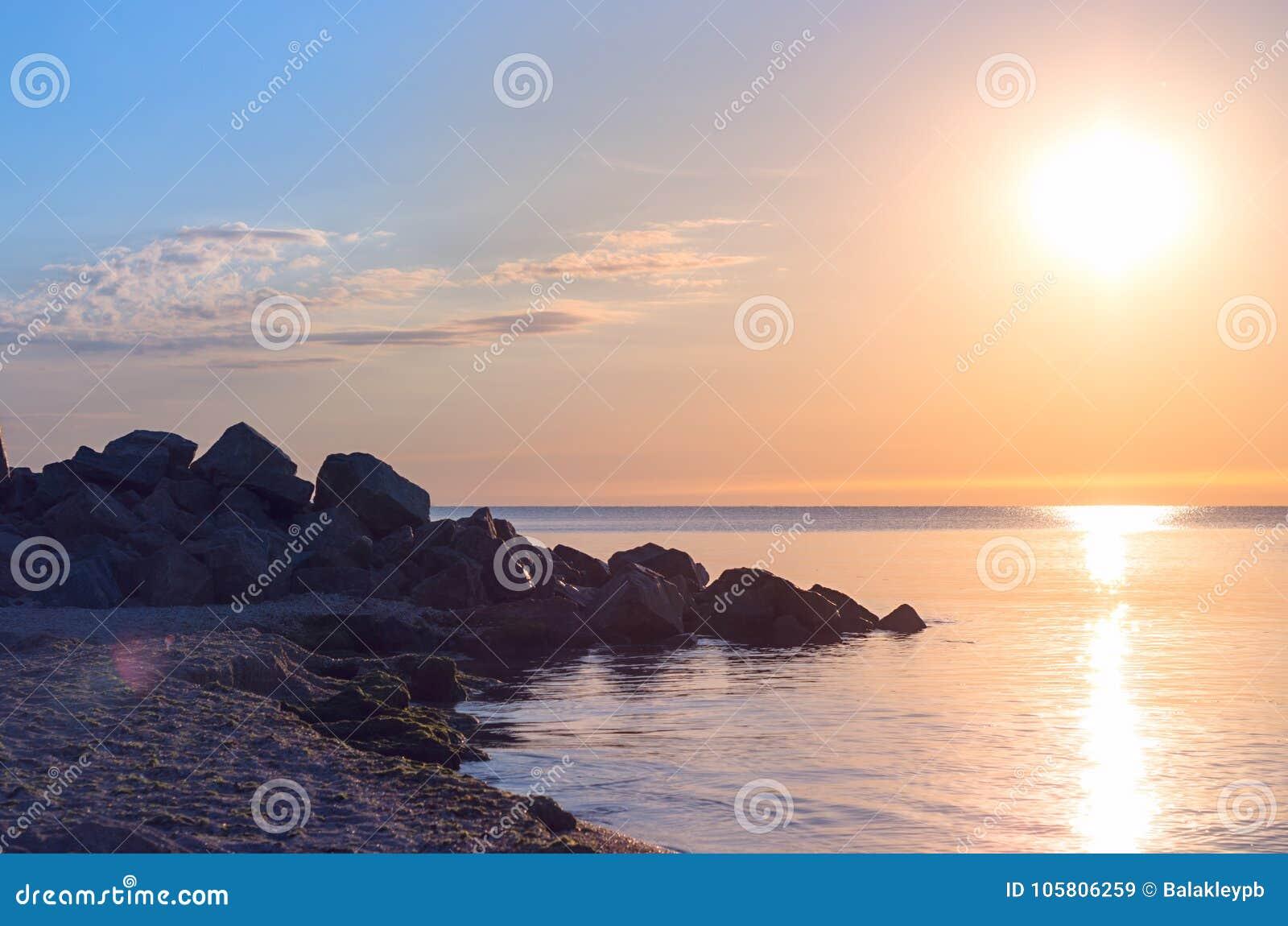 71b4a9453c Πέτρινη παραλία στην ακροθαλασσιά μπλε ουρανός οριζόντων Αντανάκλαση της  ανατολής τονισμένος