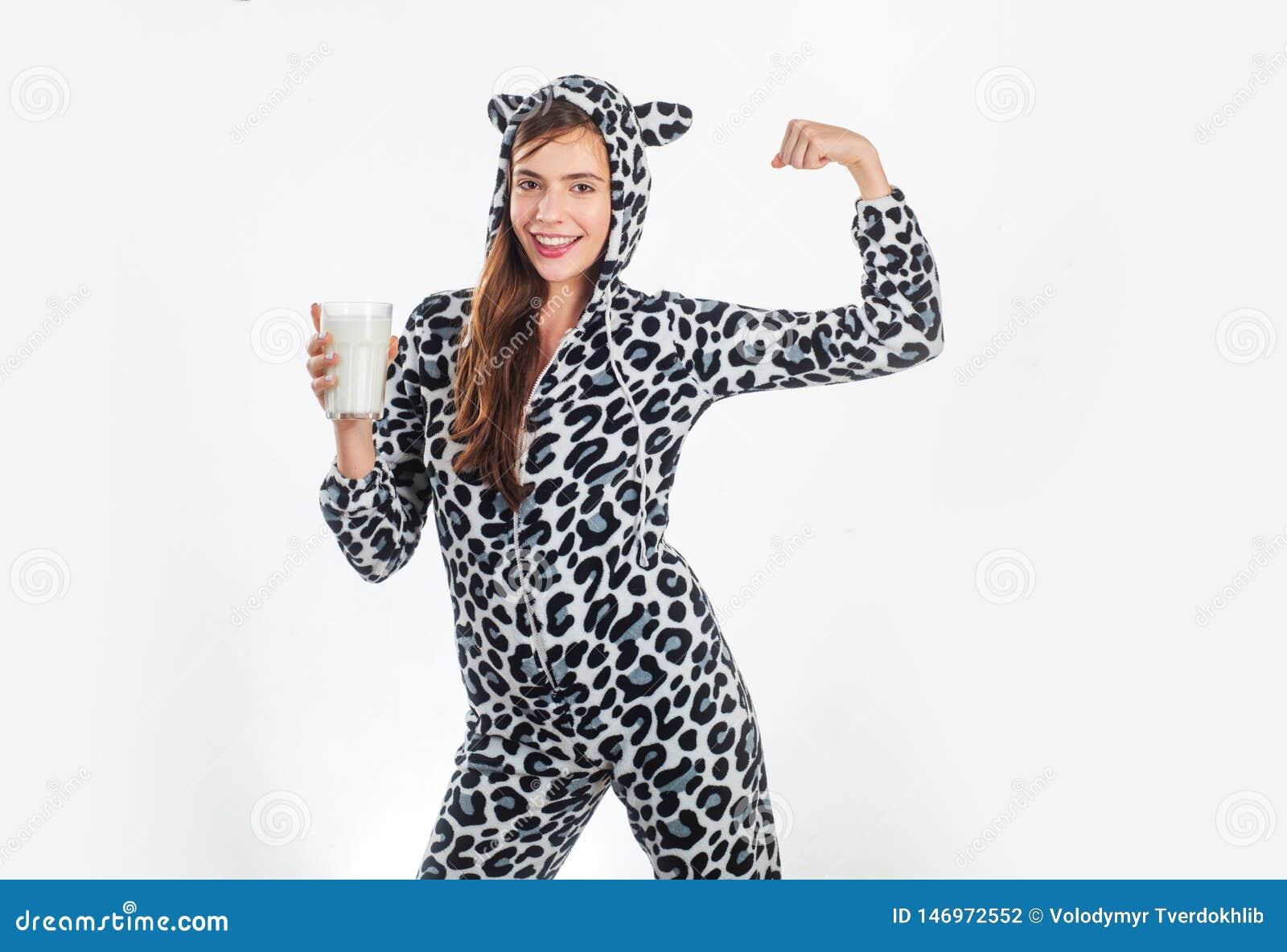 Πήρα το γάλα κοιτάζοντας στο κόμμα Όμορφο κορίτσι στο επισημασμένο ποτήρι εκμετάλλευσης κοστουμιών σχεδίου αγελάδων των γαλακτοκο