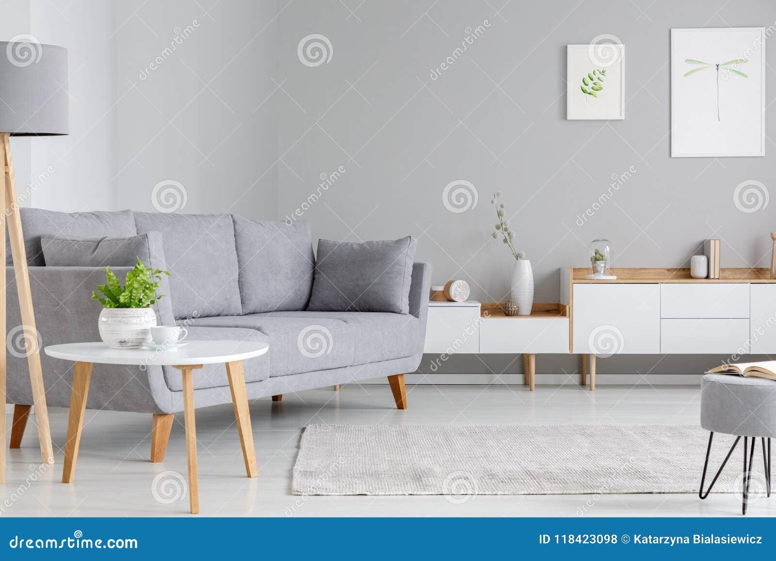 Πίνακας δίπλα στον γκρίζο καναπέ στο εσωτερικό καθιστικών scandi με τη θέση