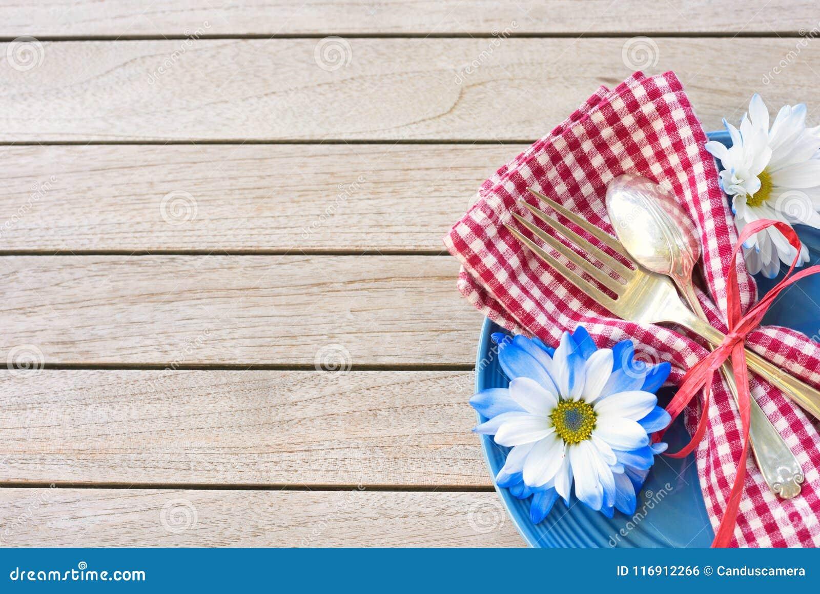 Πίνακας πικ-νίκ που θέτει στα κόκκινα άσπρα και μπλε χρώματα για τον εορτασμό την 4η Ιουλίου στον ξύλινο πίνακα υποβάθρου πινάκων