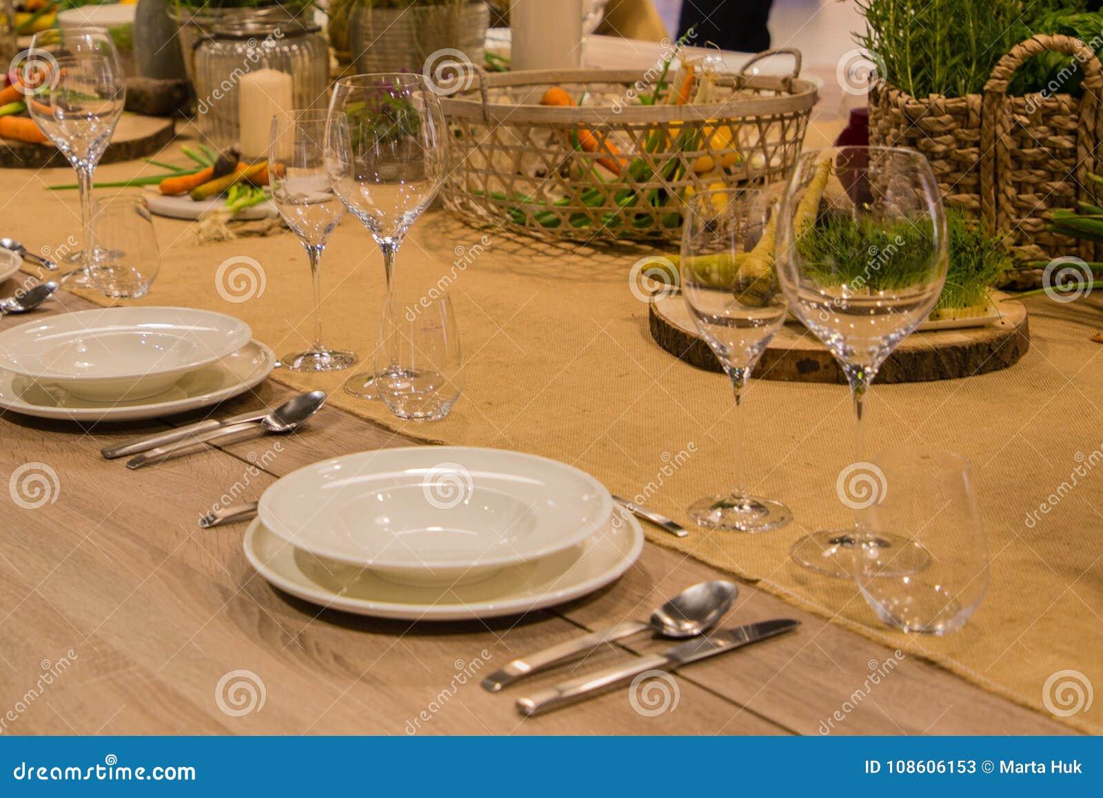 Πίνακας στο εστιατόριο που εξυπηρετείται για διάφορα πρόσωπα με τα γυαλιά και τα πιάτα