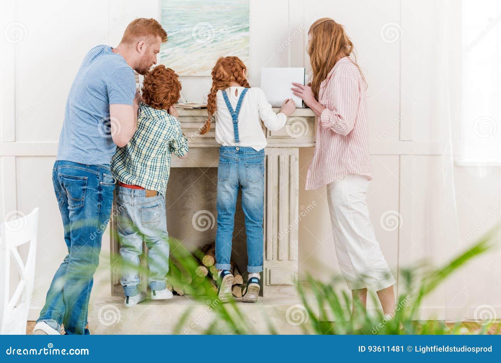 Πίσω άποψη της redhead οικογένειας με δύο παιδιά που στέκονται μαζί κοντά στην εστία και που διαβάζουν τα περιοδικά
