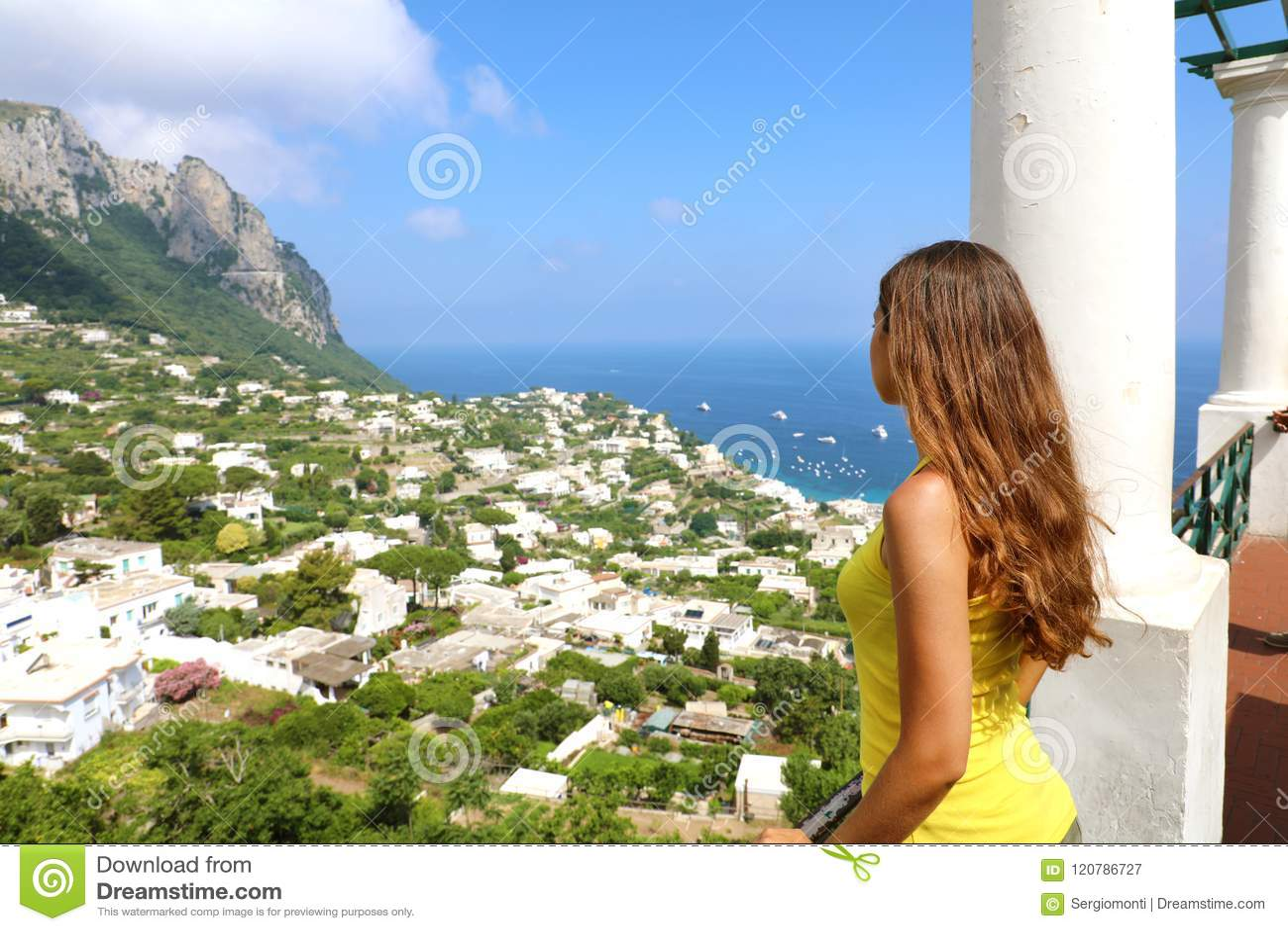 Πίσω άποψη του όμορφου κοριτσιού που εξετάζει τη θέα Capri από το πεζούλι, νησί Capri, Ιταλία