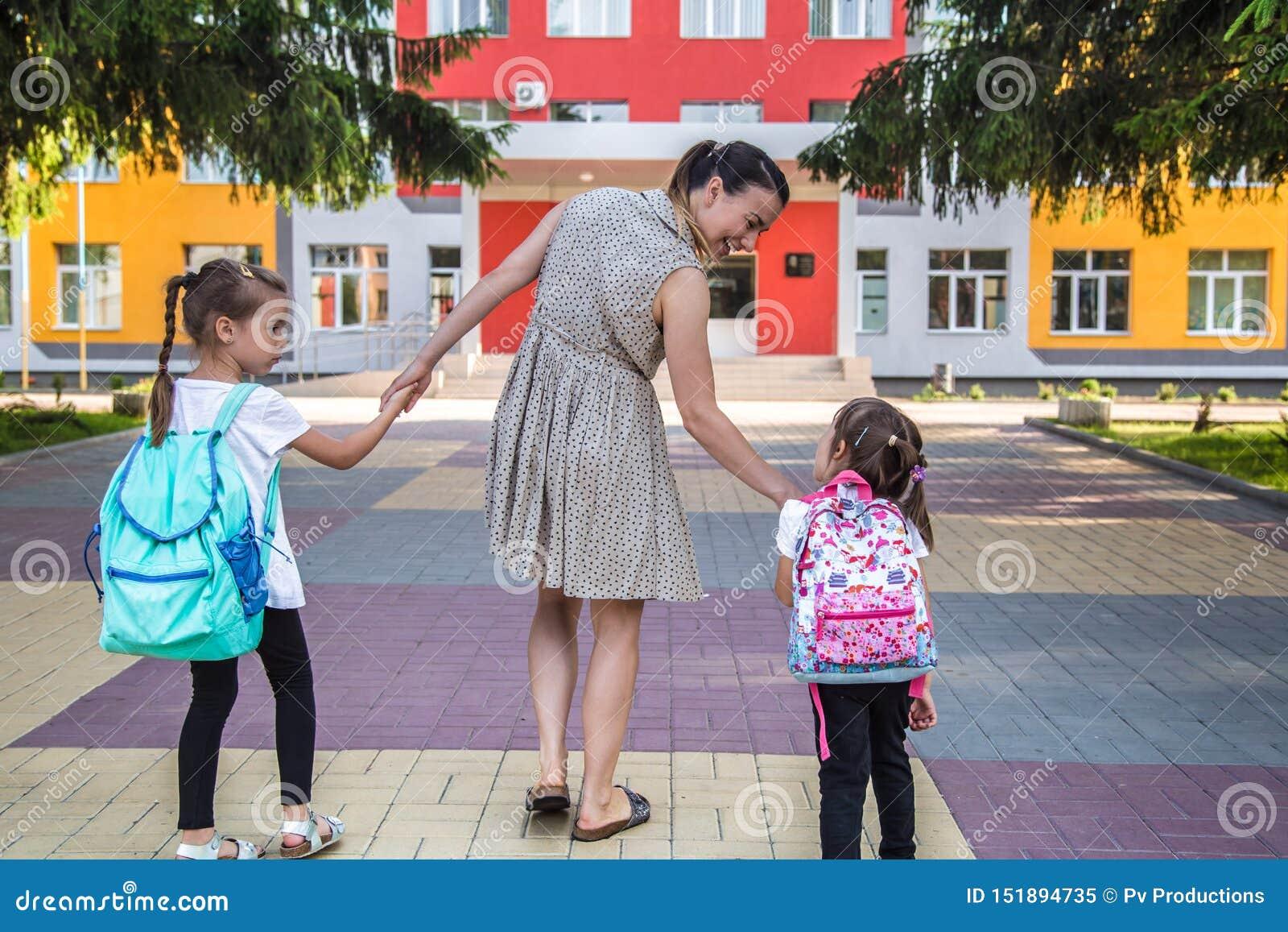 Πίσω στην έννοια σχολικής εκπαίδευσης με τα παιδιά κοριτσιών, στοιχειώδεις σπουδαστές, φέρνοντας σακίδια πλάτης που πηγαίνουν στη