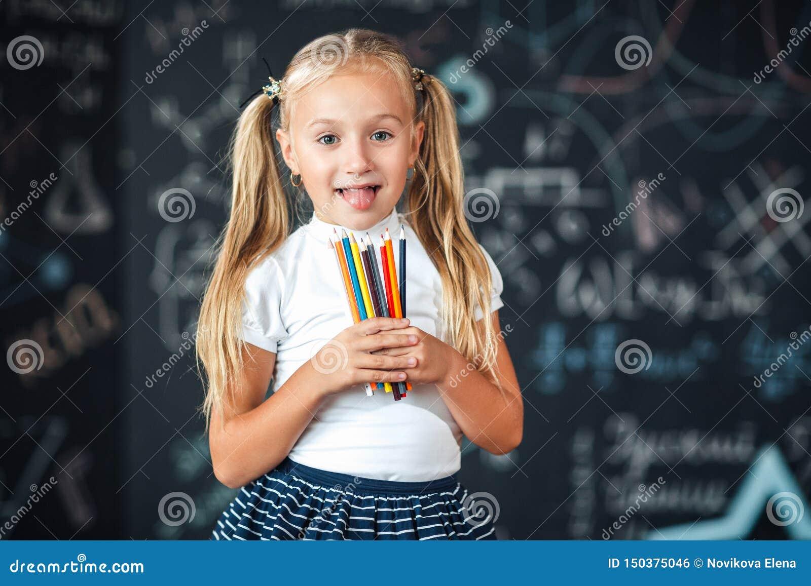 Πίσω στο σχολείο! Ένα μικρό κορίτσι στέκεται με τα μολύβια στα χέρια της ενάντια στον πίνακα κιμωλίας με τους σχολικούς τύπους στ