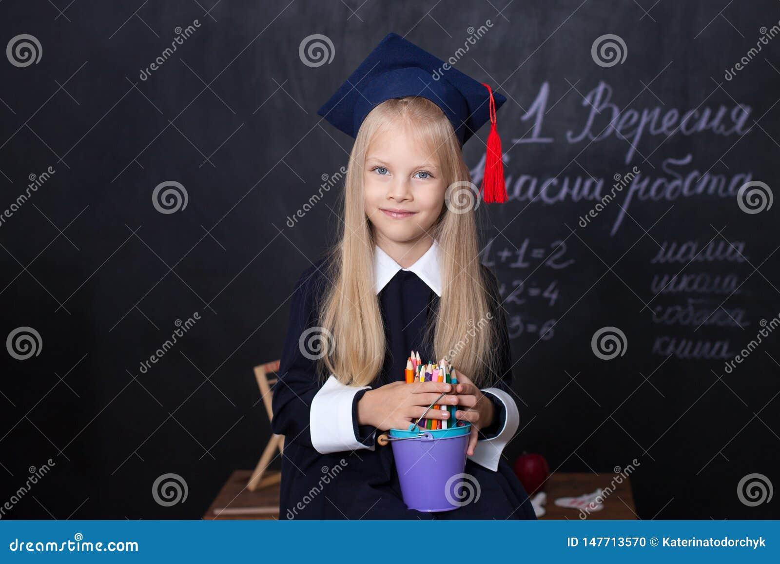 Πίσω στο σχολείο! Εύθυμο μικρό κορίτσι στο σχολείο σε ένα μαύρο υπόβαθρο Να εξετάσει τη κάμερα Σχολική έννοια Μαθήτρια στο γ