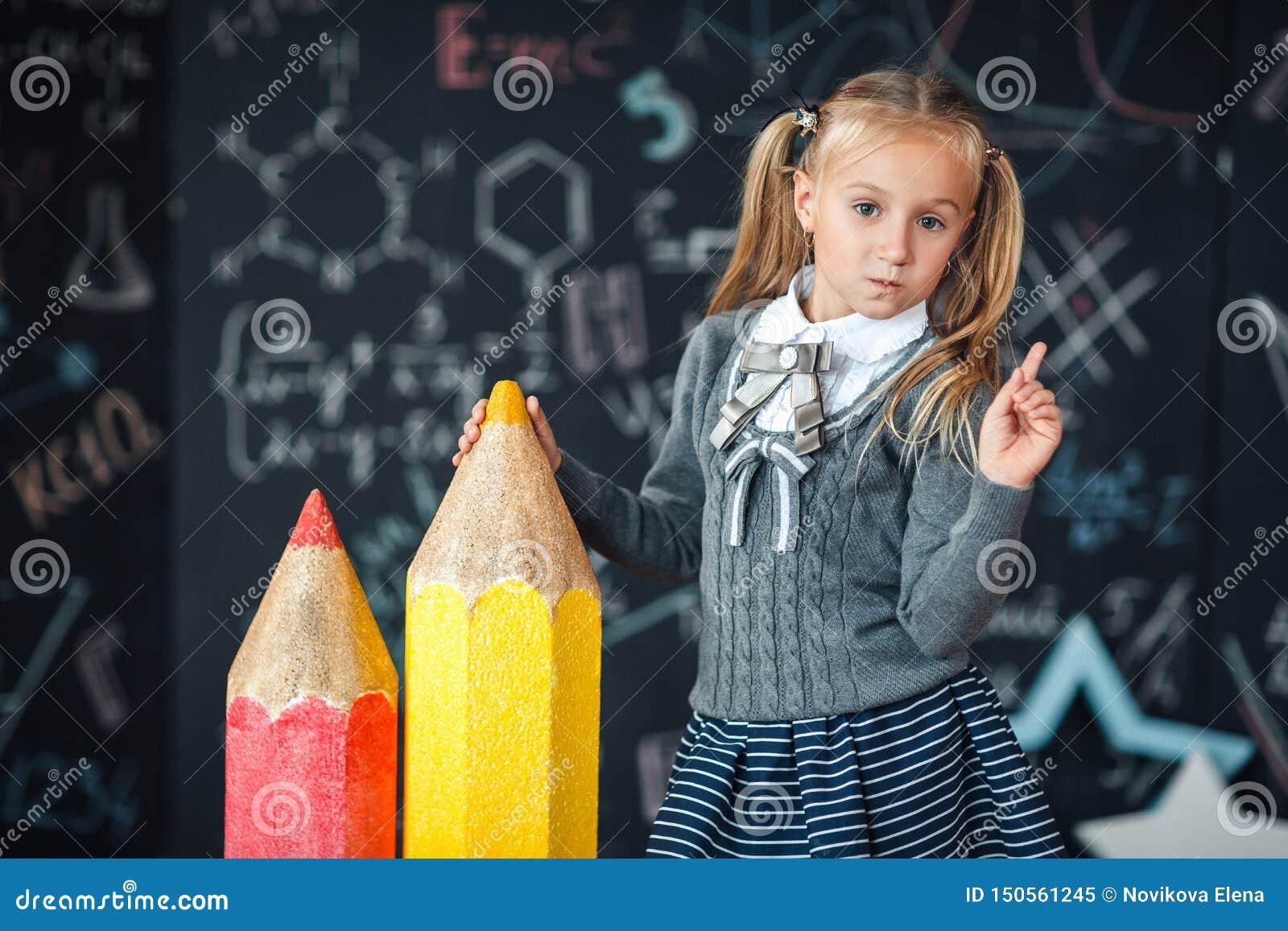 Πίσω στο σχολείο! Το λίγο ξανθό κορίτσι στη σχολική στολή στέκεται με δύο πολύ μεγάλα μολύβια στο floore ενάντια στον πίνακα κιμω