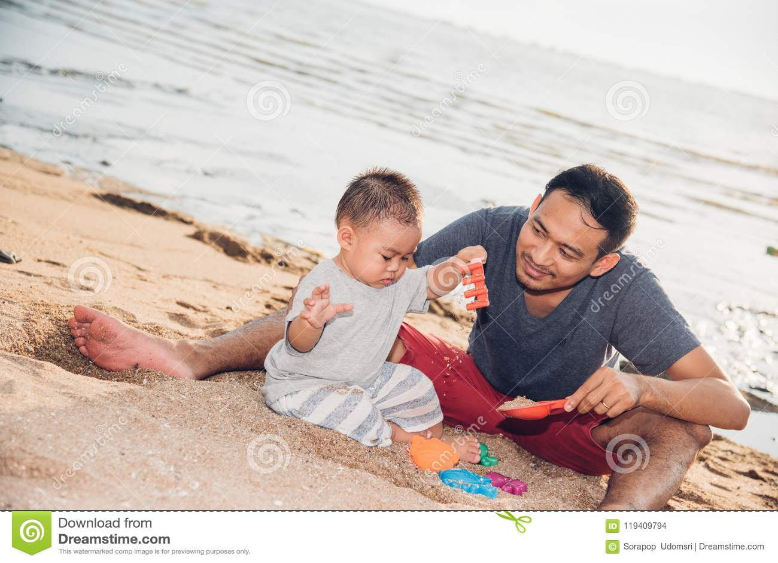 Παίζοντας διασκέδαση μπαμπάδων αγοράκι και πατέρων στην παραλία άμμου