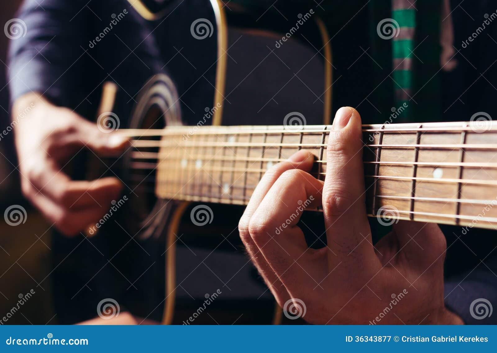 Παίζοντας μουσική ατόμων στη μαύρη ξύλινη ακουστική κιθάρα