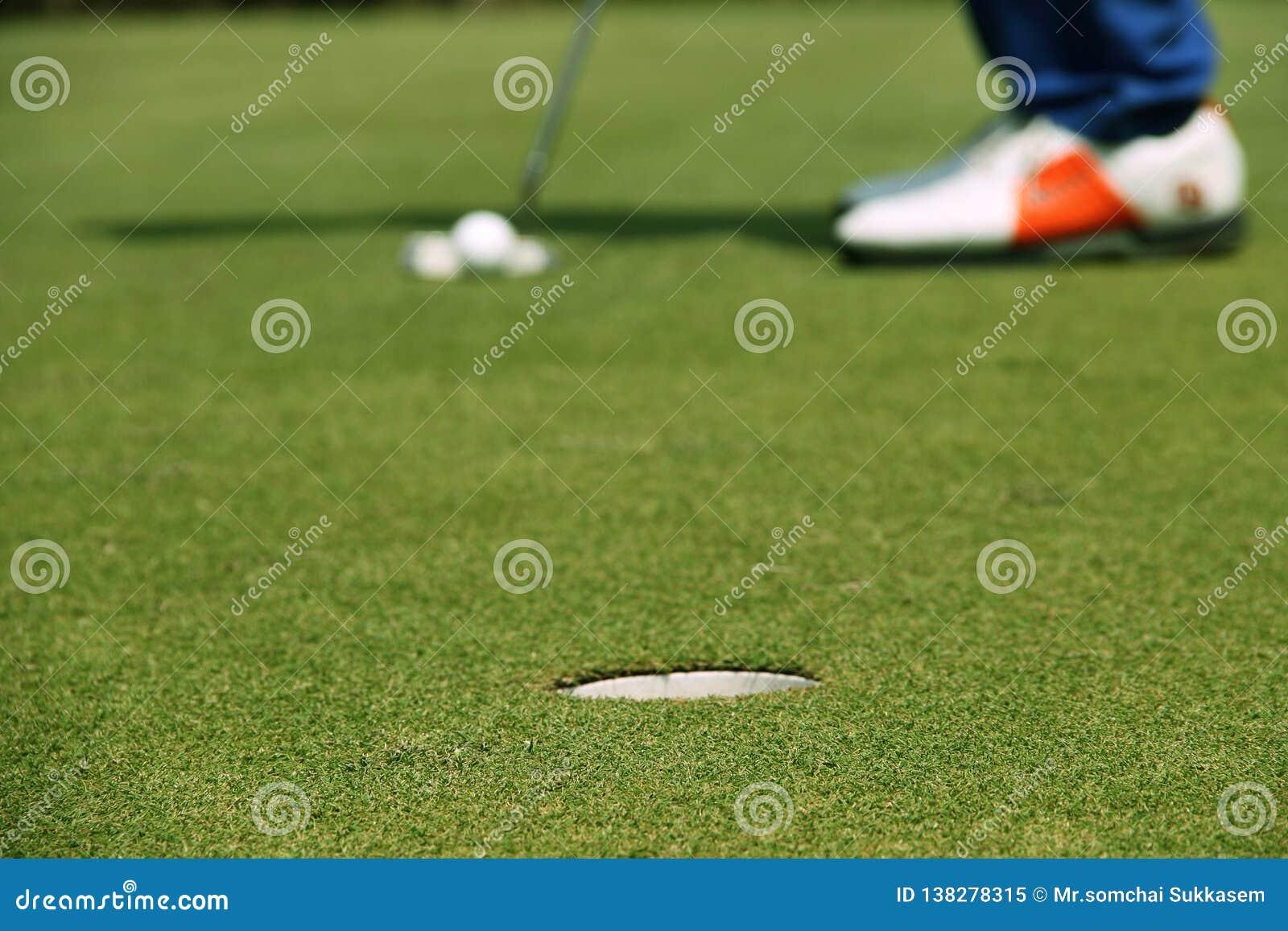 Παίκτης γκολφ που βάζει τη σφαίρα γκολφ στο πράσινο γκολφ