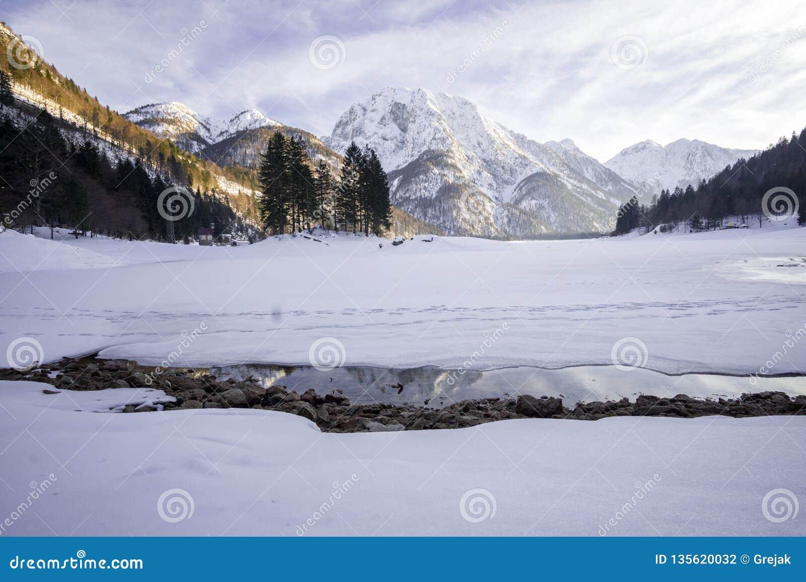 Παγωμένη λίμνη που καλύπτεται στο χιόνι με το χιονώδες βουνό στην πλάτη