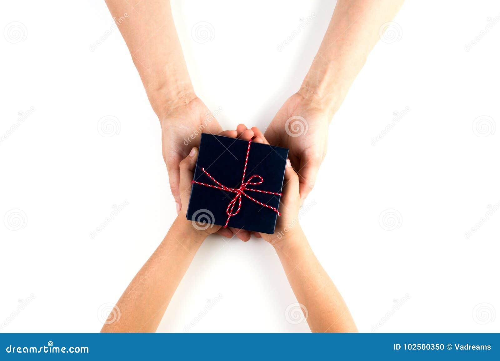 Παιδί και ενήλικα χέρια που δίνουν και που λαμβάνουν ένα παρόν