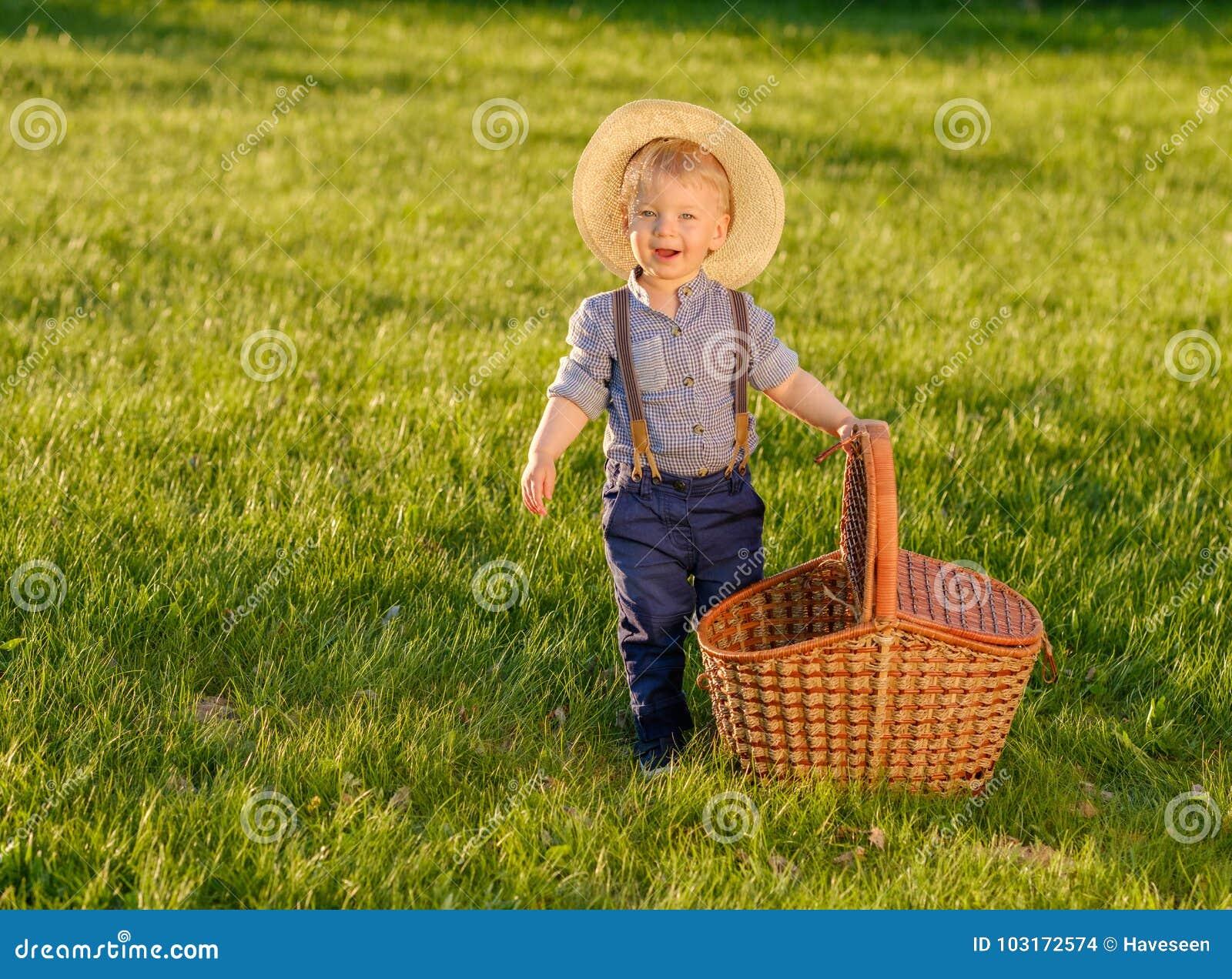 Παιδί μικρών παιδιών υπαίθρια Αγοράκι ενός έτους βρεφών που φορά το καπέλο αχύρου με το καλάθι πικ-νίκ