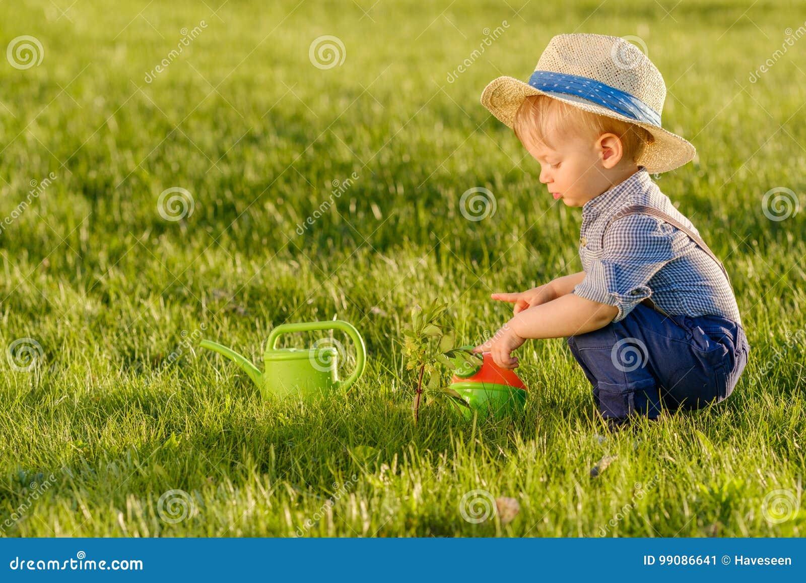 Παιδί μικρών παιδιών υπαίθρια Το αγοράκι ενός έτους βρεφών που φορά το καπέλο αχύρου που χρησιμοποιεί το πότισμα μπορεί