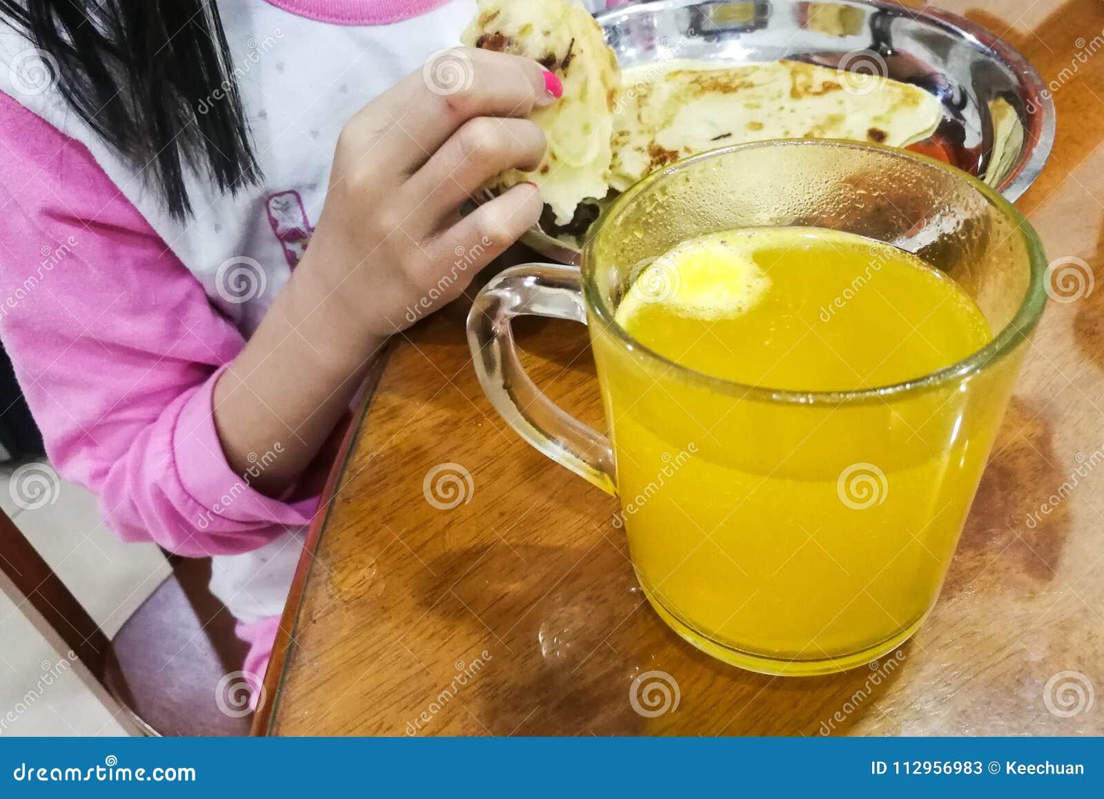 Παιδί που έχει το πρόγευμα με το γυαλί της ζωηρής ταμπλέτας βιταμίνης C