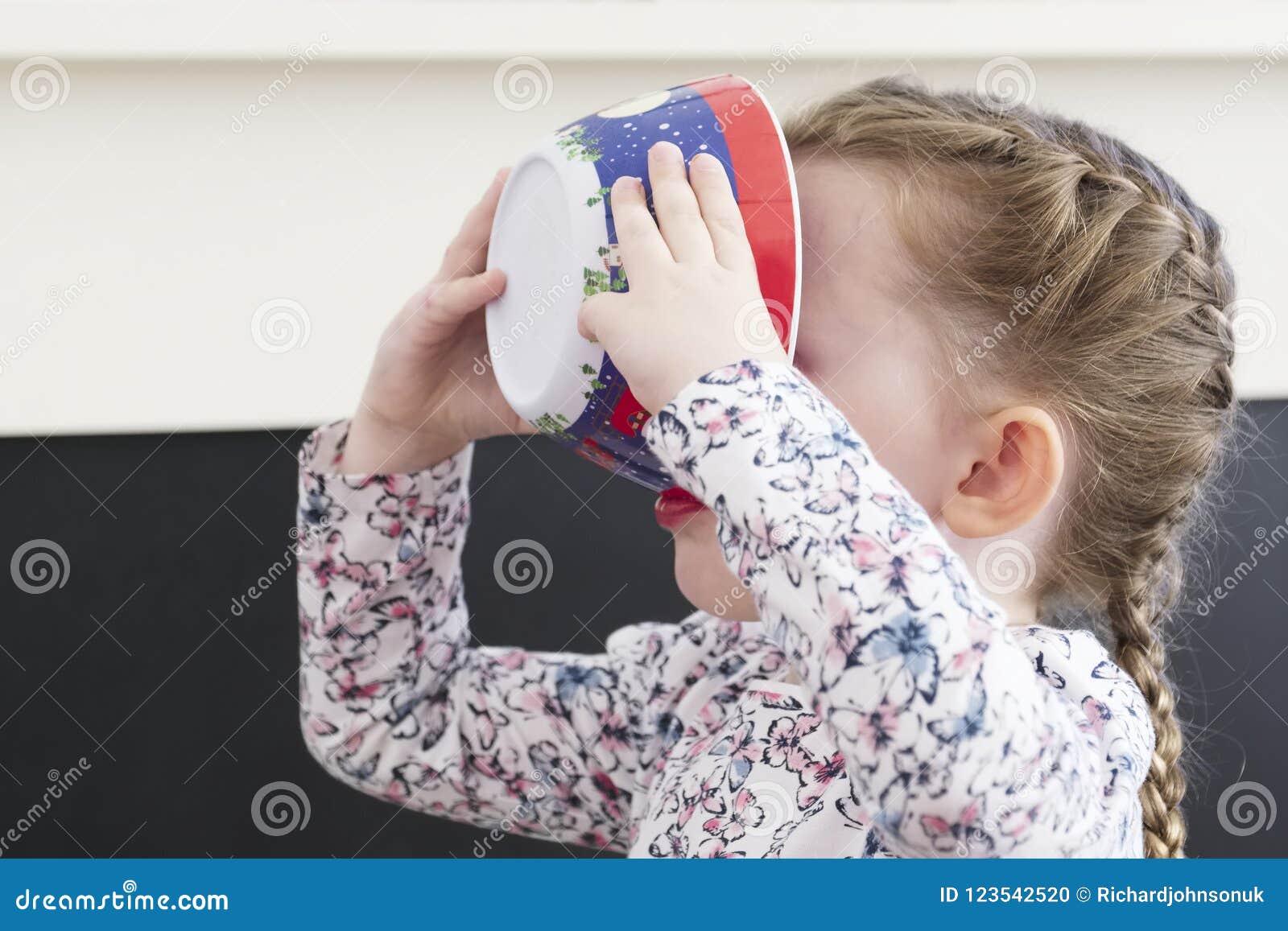 Παιδί που τρώει από το πιάτο που κρατιέται στο πρόσωπό της