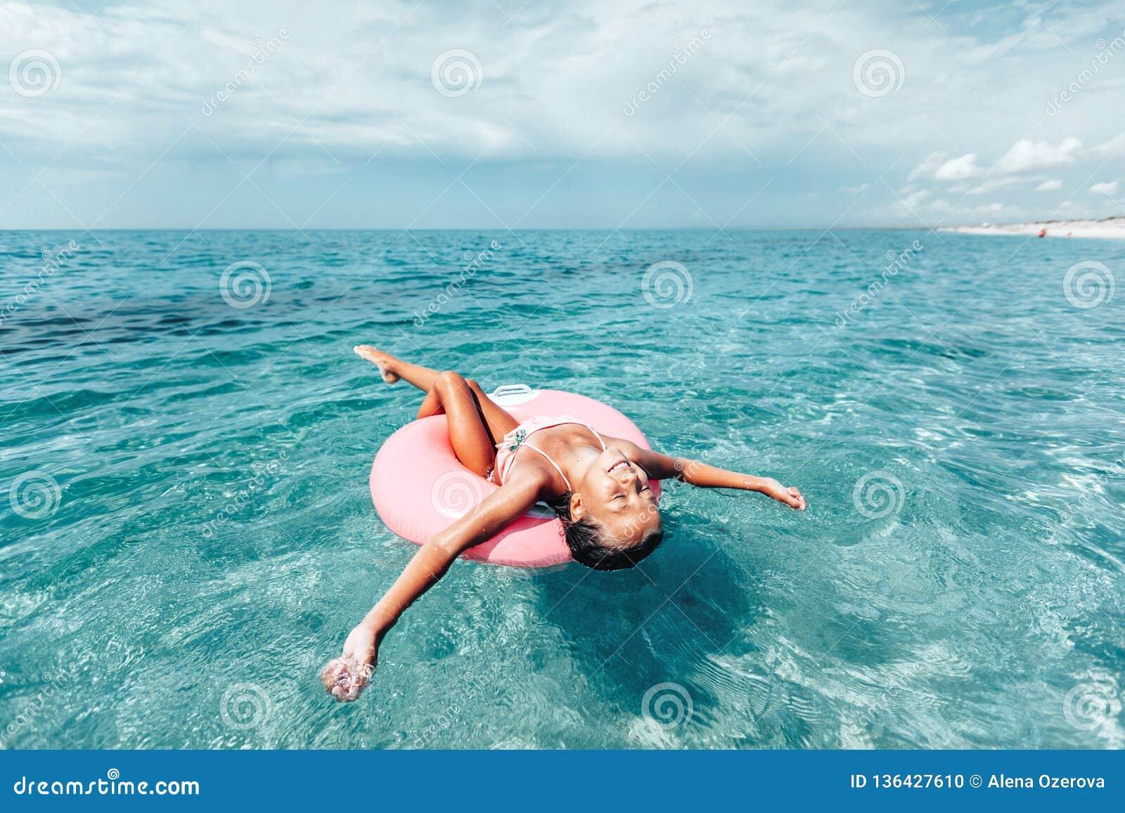 Παιδί στη χαλάρωση lilo στην παραλία