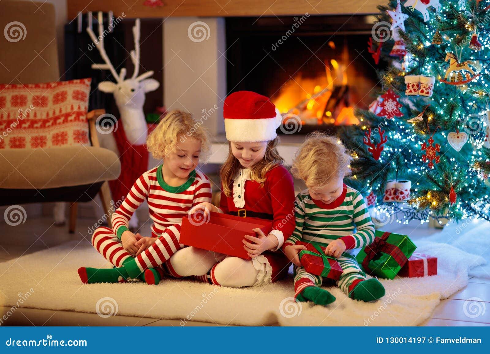 Παιδί στο χριστουγεννιάτικο δέντρο Παιδιά στην εστία στα Χριστούγεννα