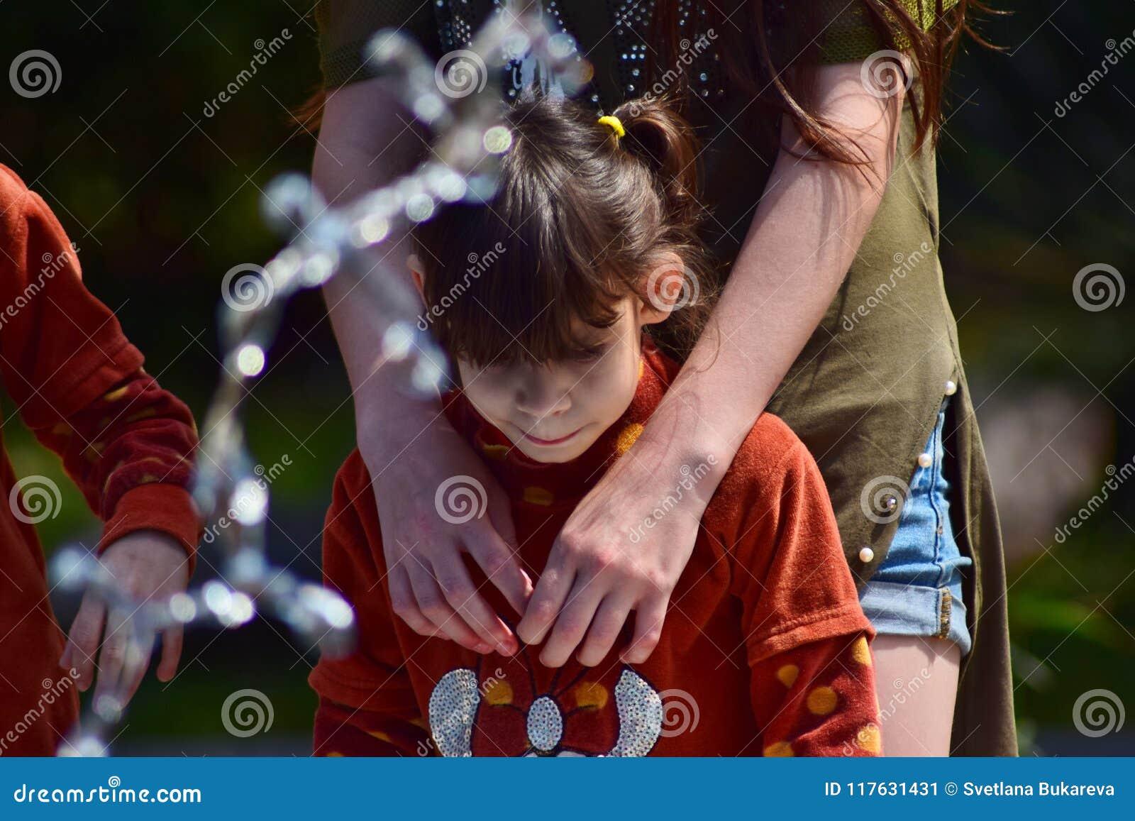Παιδιά από την ίδια οικογένεια που στέκεται στην πηγή στο πάρκο πόλεων