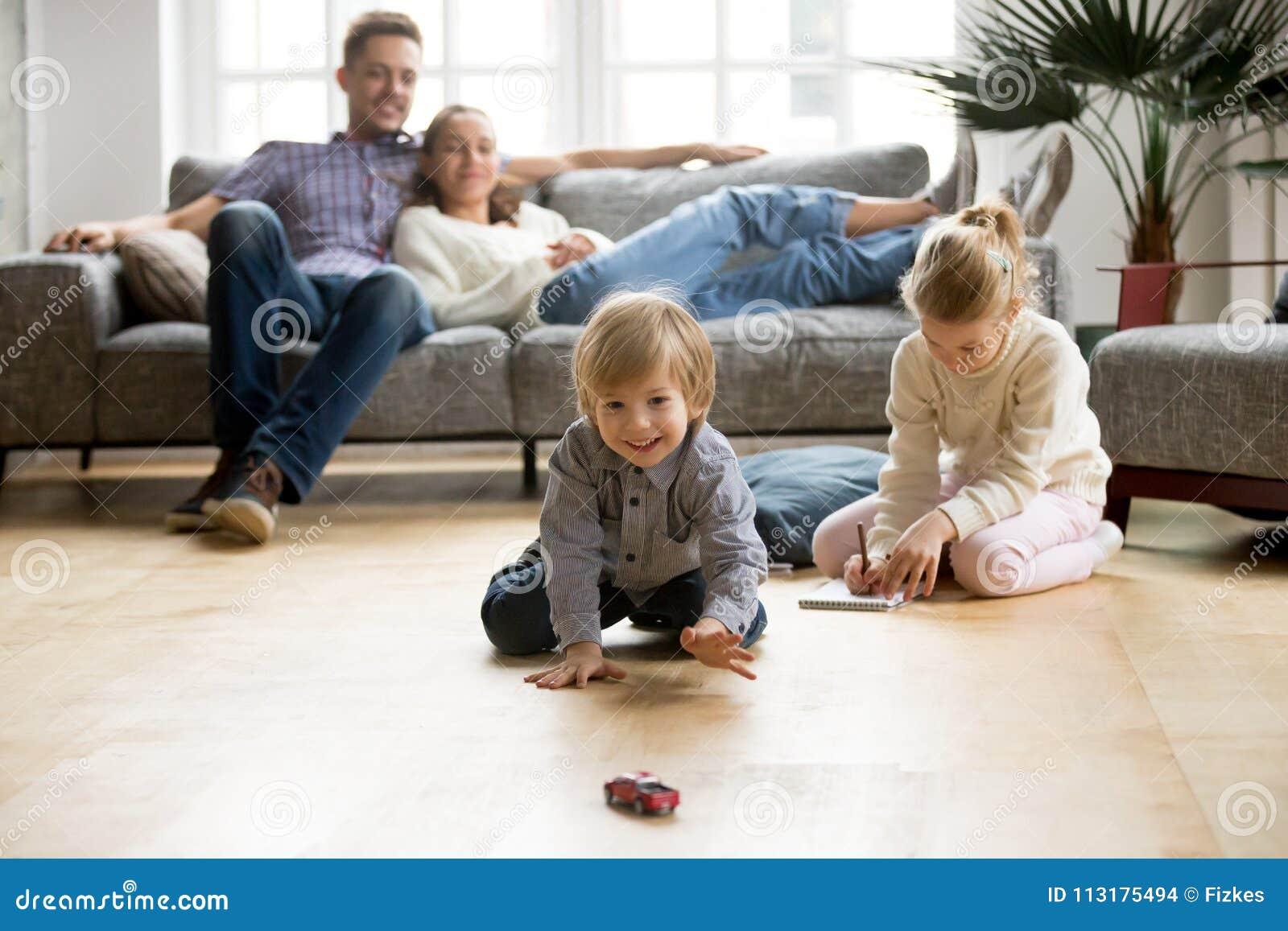 Παιδιά που παίζουν στο πάτωμα, γονείς που χαλαρώνει στον καναπέ στο σπίτι