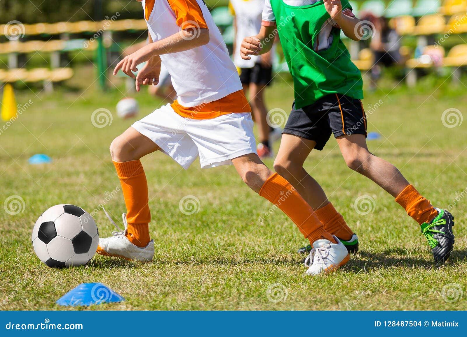 Παιδιά που παίζουν τη σφαίρα ποδοσφαίρου στον τομέα χλόης Ανταγωνισμός ποδοσφαίρου μεταξύ δύο παιδιών