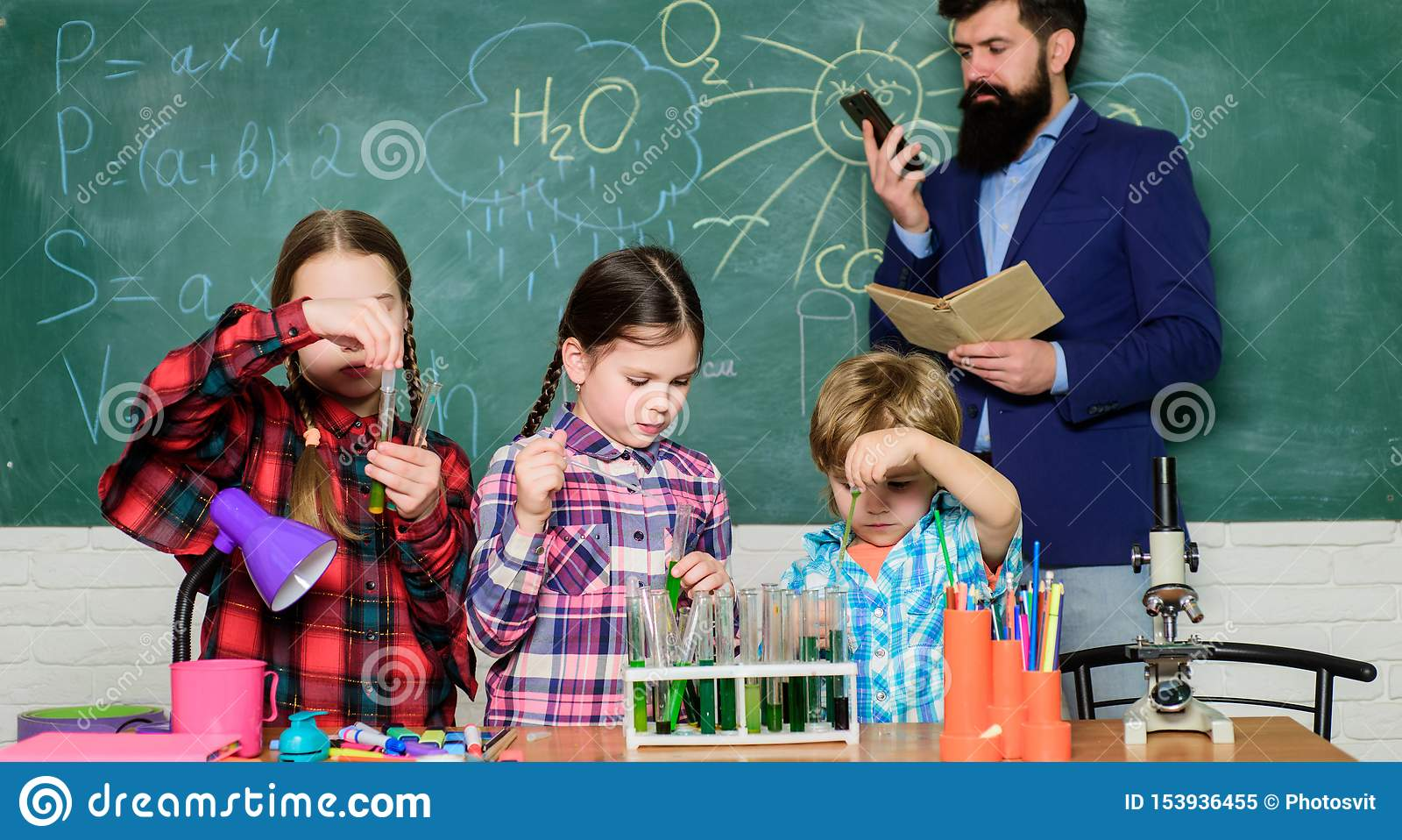 Παιδιά στη χημεία εκμάθησης παλτών εργαστηρίων στο σχολικό εργαστήριο εργαστήριο χημείας ευτυχής δάσκαλος παιδιών o παραγωγή