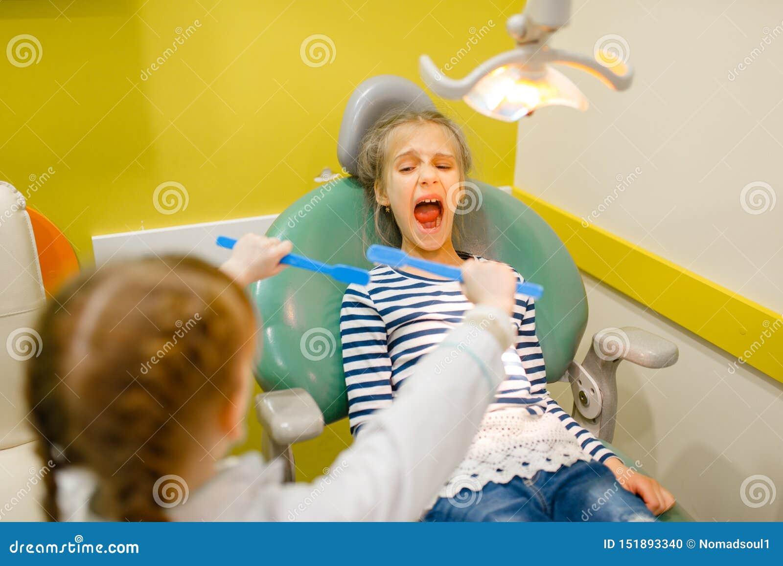 Παιδιά στον ομοιόμορφο παίζοντας οδοντίατρο, χώρος για παιχνίδη