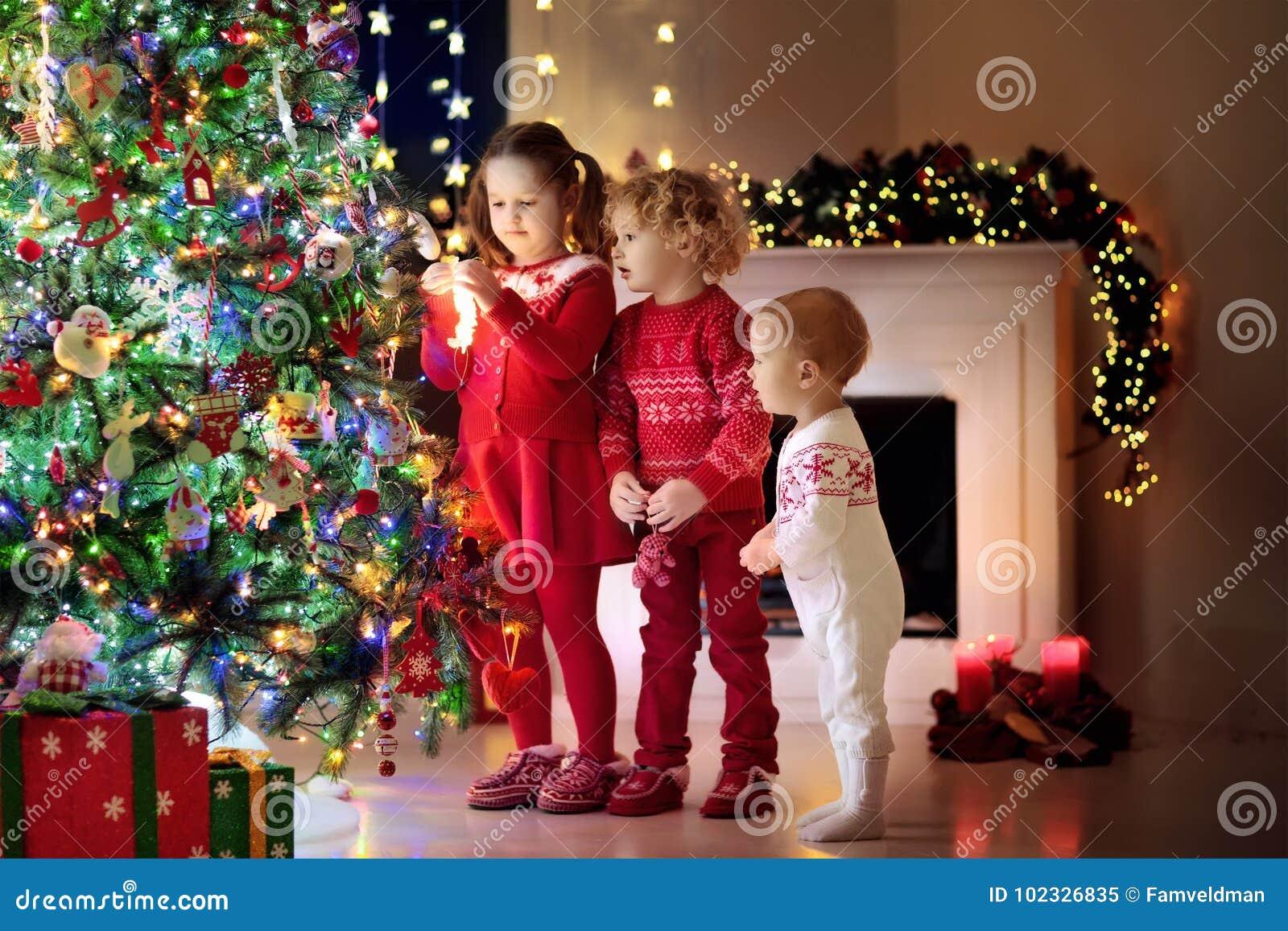 Παιδιά στο χριστουγεννιάτικο δέντρο Παιδιά στην εστία στην παραμονή Χριστουγέννων