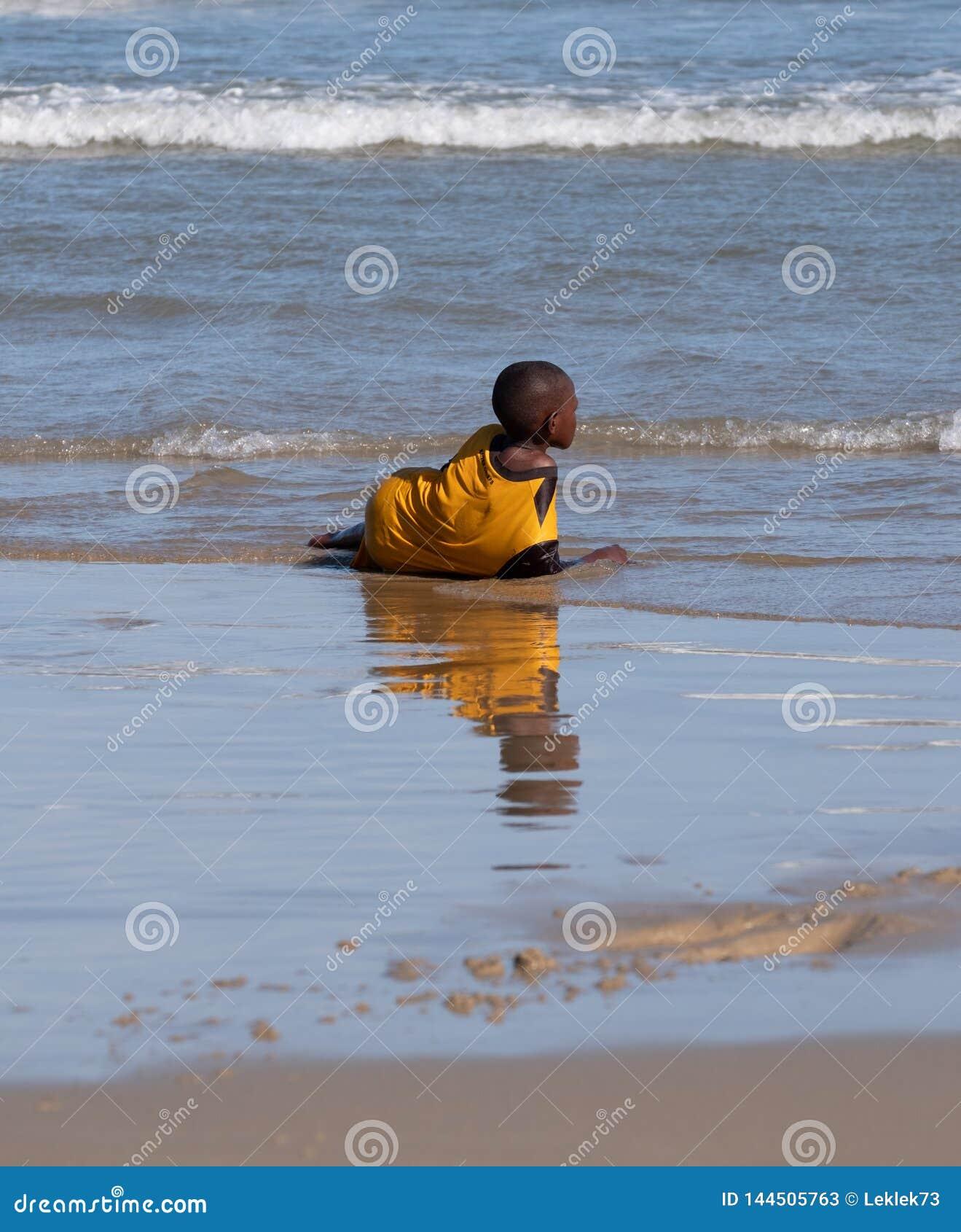 Παιδικά παιχνίδια στα κύματα στη δεύτερη παραλία, λιμένας ST Johns στην άγρια ακτή στο Transkei, Νότια Αφρική