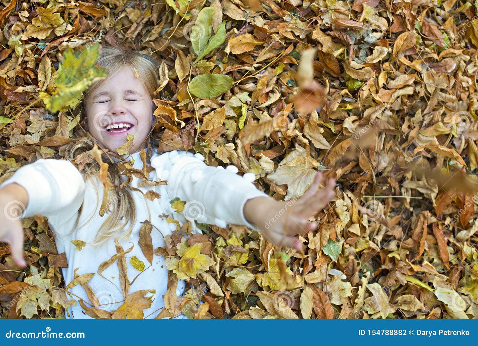 Παιχνίδια παιδιών στο πάρκο φθινοπώρου Παιδί που ρίχνει τα κίτρινα και κόκκινα φύλλα Μικρό κορίτσι με τη βαλανιδιά και το φύλλο σ