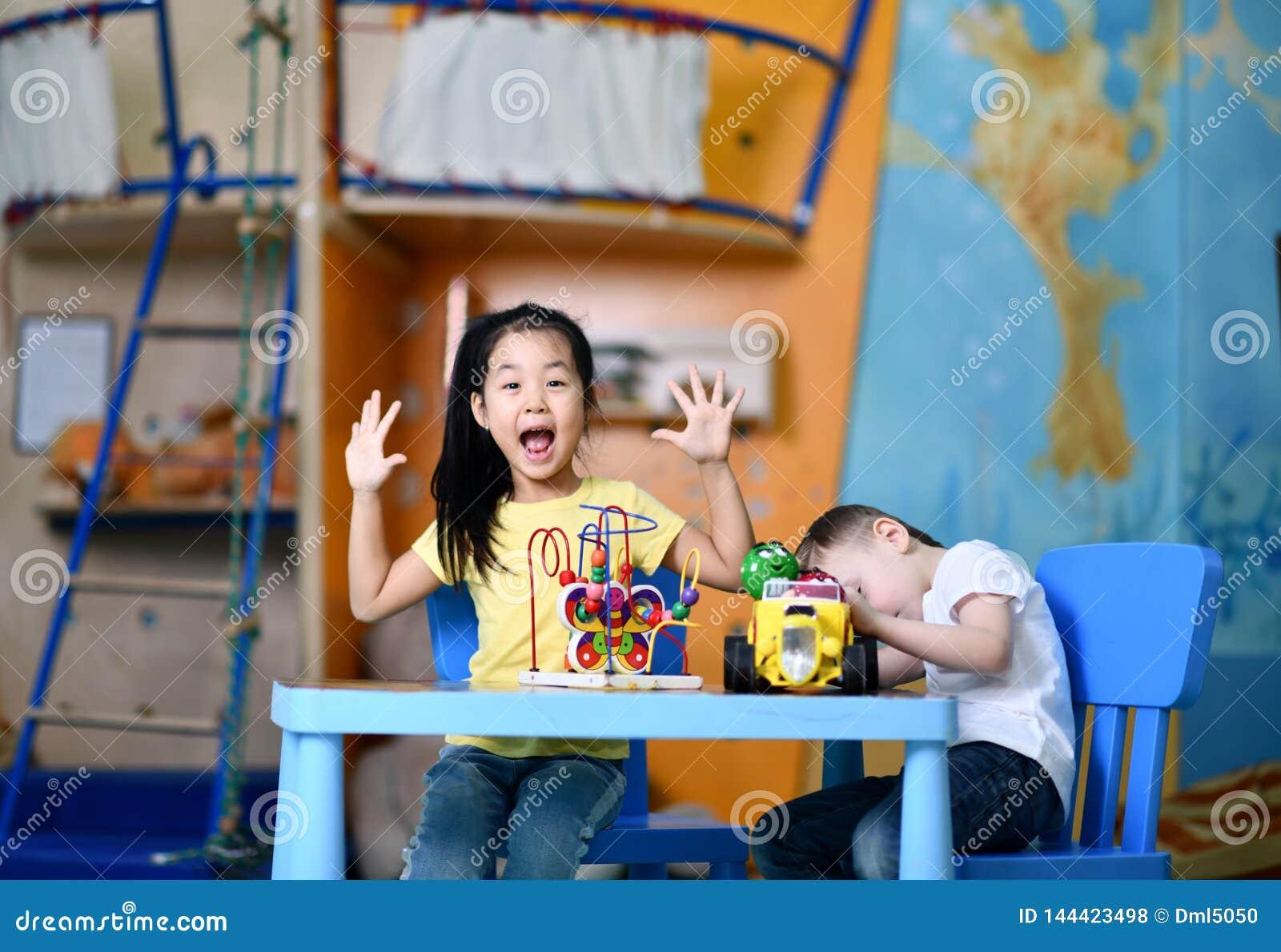 Παιχνίδι αγοριών και κοριτσιών δύο χαρούμενο παιδιών ενθουσιωδώς στον πίνακα με τα παιχνίδια
