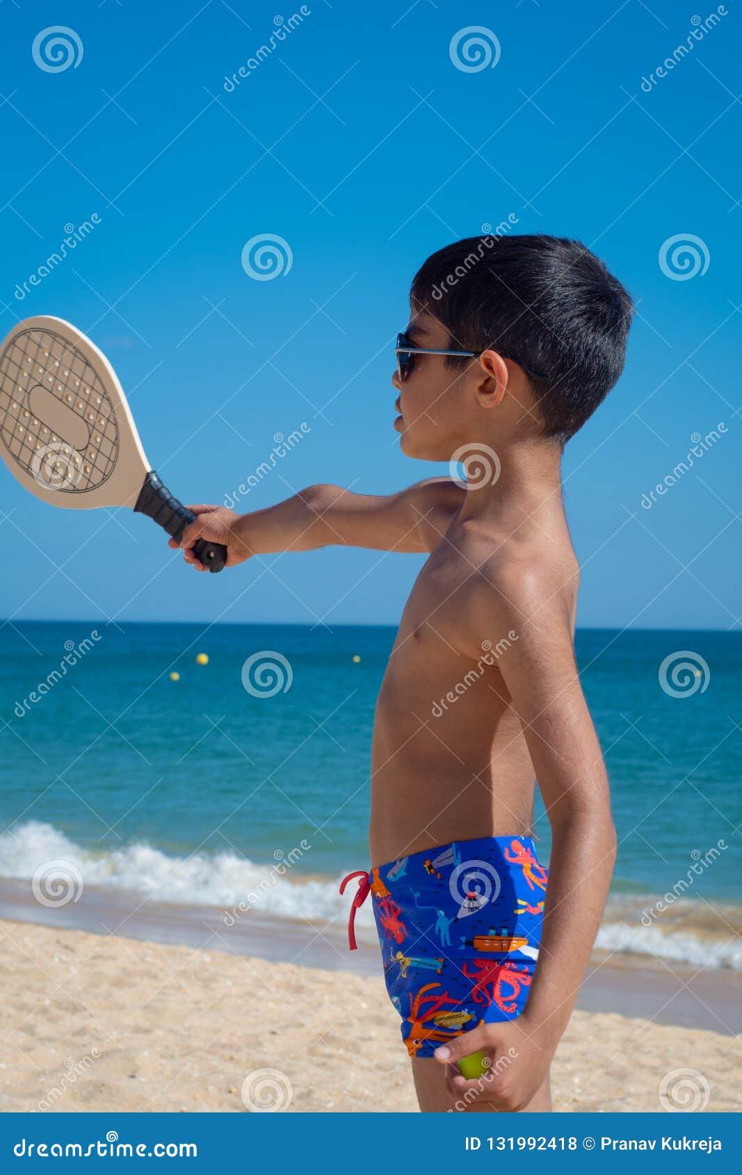 Παιχνίδι αγοριών με τη ρακέτα σε μια παραλία στις διακοπές