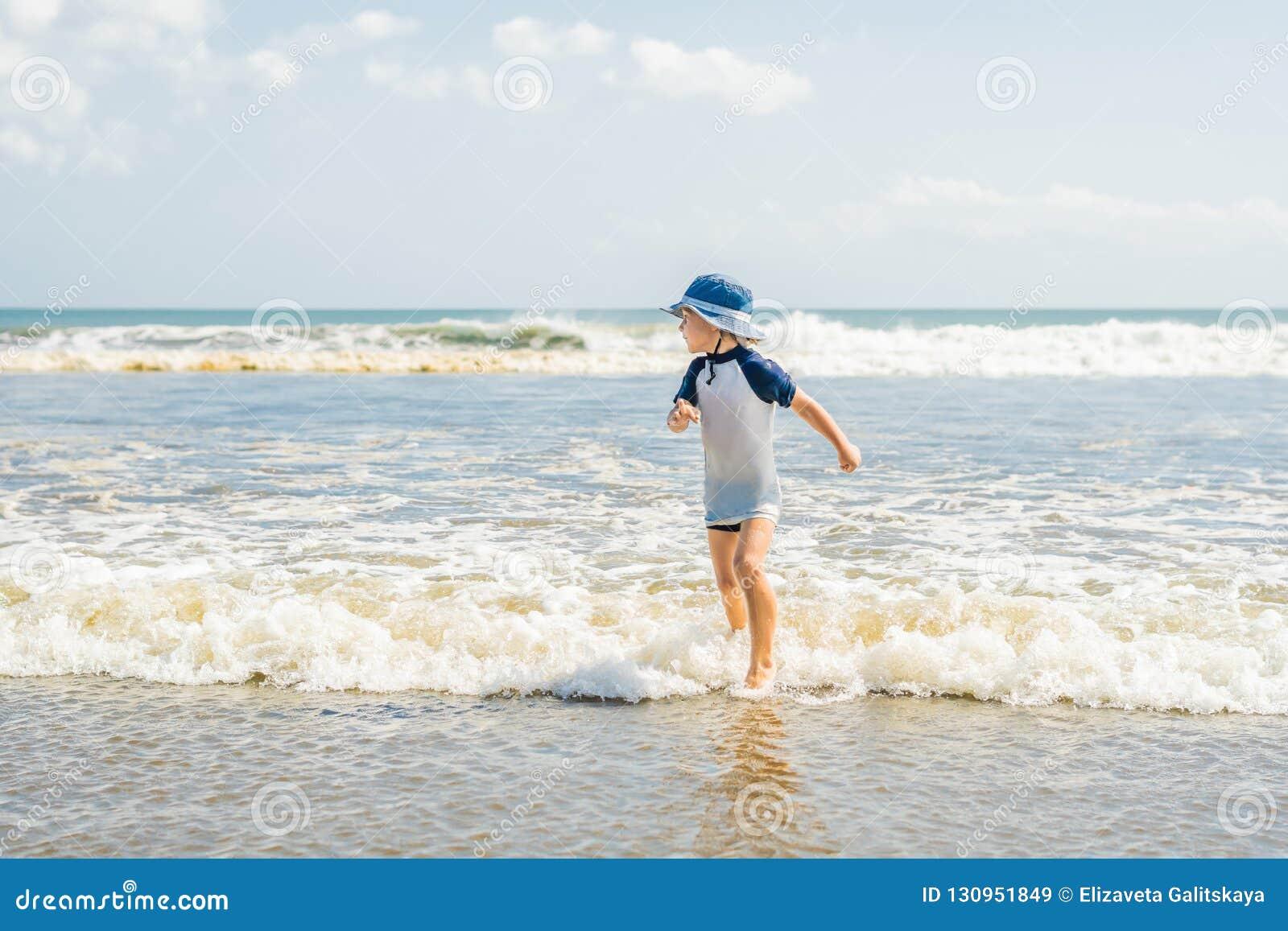 Παιχνίδι αγοριών στην παραλία στο νερό
