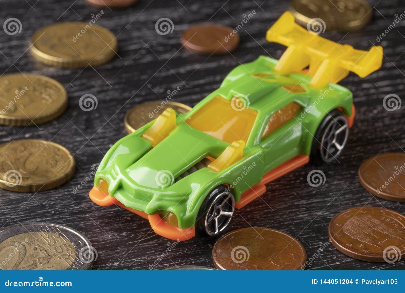 Παιχνίδι αυτοκινήτων και ευρο- νομίσματα σε ένα σκοτεινό ξύλινο υπόβαθρο