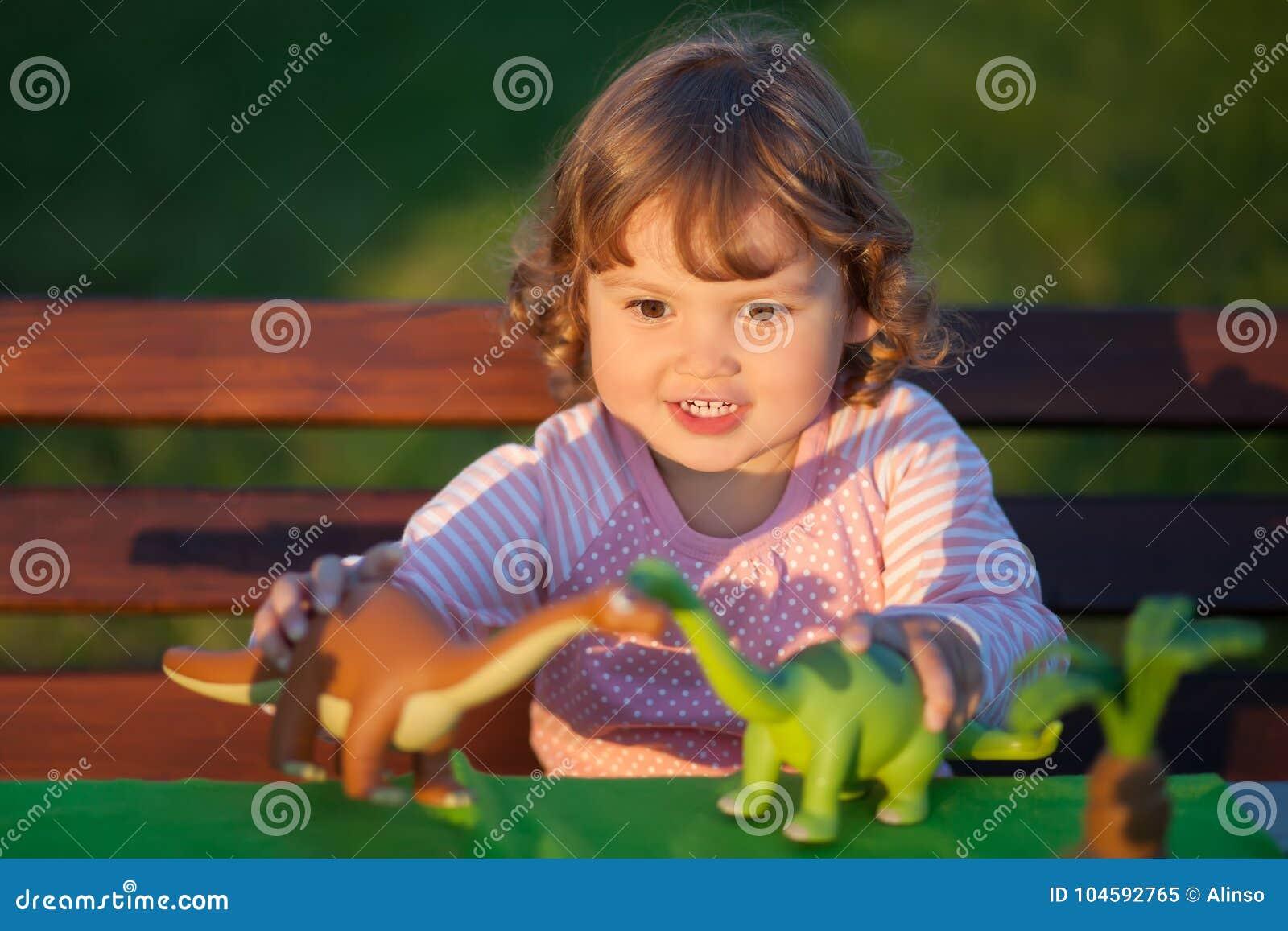 Παιχνίδι παιδιών μικρών παιδιών με έναν δεινόσαυρο παιχνιδιών
