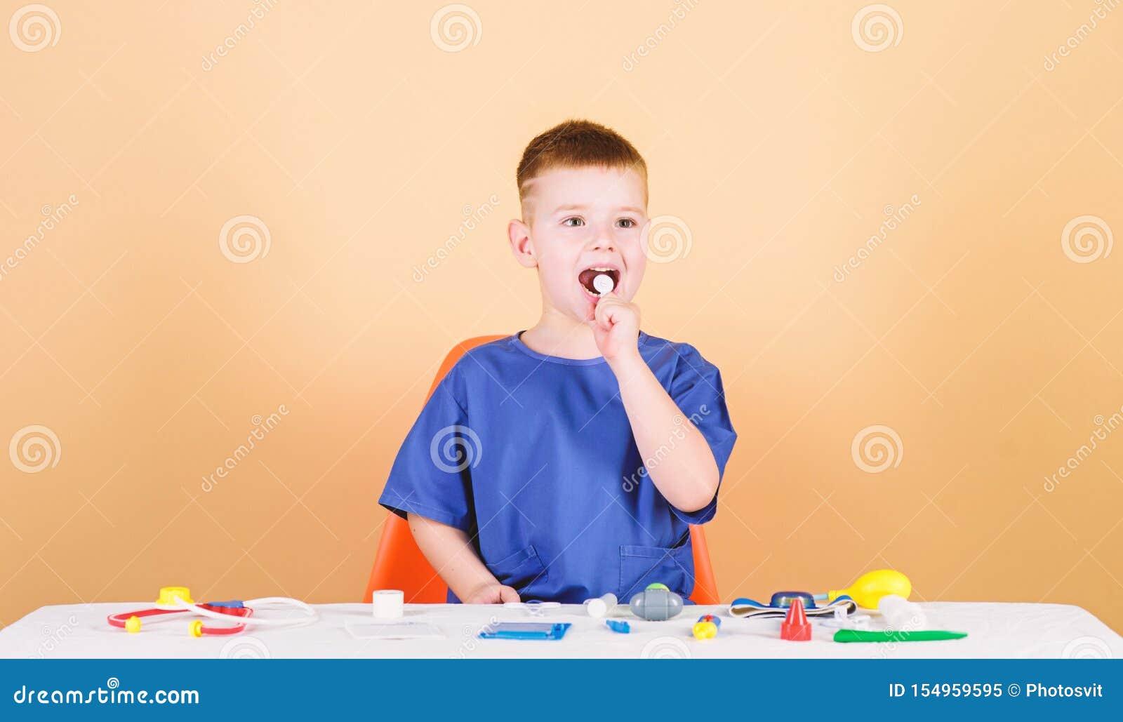 Παιχνίδι παιχνιδιού Αγοριών χαριτωμένη σταδιοδρομία γιατρών παιδιών μελλοντική Υγιής ζωή Το παιδί λίγος γιατρός κάθεται τον πίνακ
