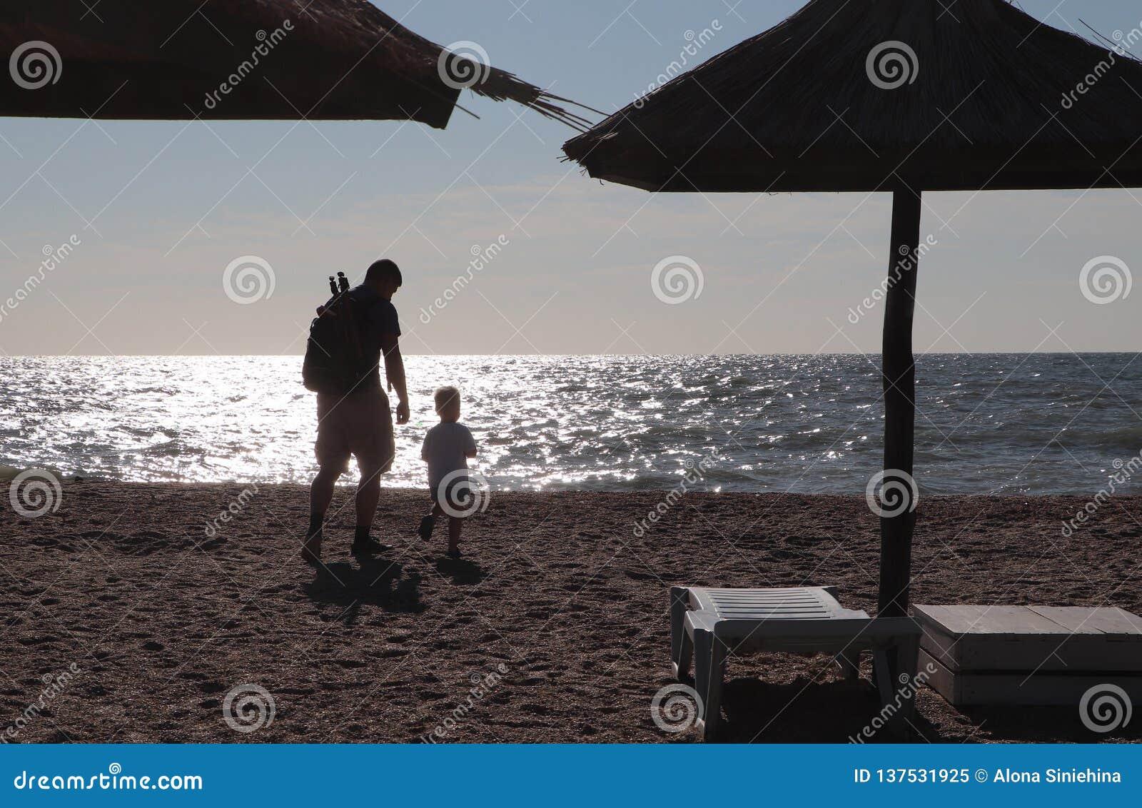 Παιχνίδι πατέρων και αγοριών στην παραλία στο χρόνο ηλιοβασιλέματος, έννοια της φιλικής οικογένειας
