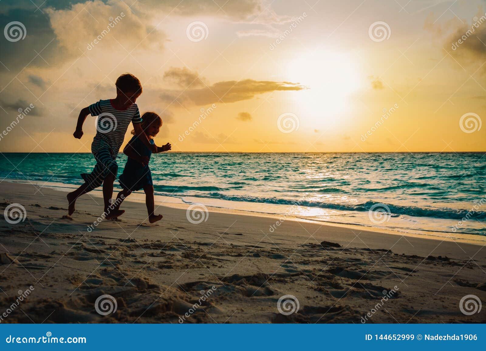 Παιχνίδι τρεξίματος μικρών παιδιών και κοριτσιών στην παραλία ηλιοβασιλέματος
