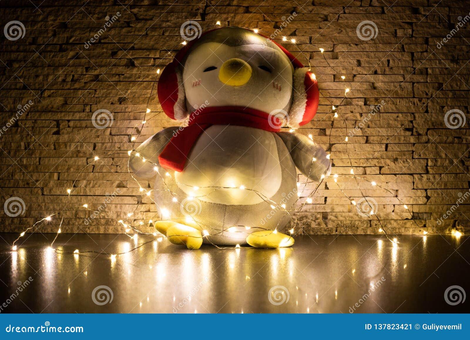 Παιχνίδι Penguin που περιβάλλεται από τη γιρλάντα με το διακοσμημένο υπόβαθρο τοίχων φωτογραφία στο σκοτάδι