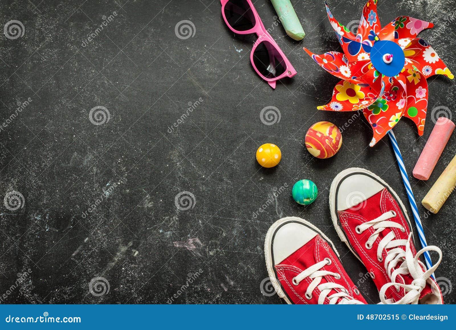 Παιχνίδια και κόκκινα πάνινα παπούτσια στο μαύρο πίνακα κιμωλίας - παιδική ηλικία