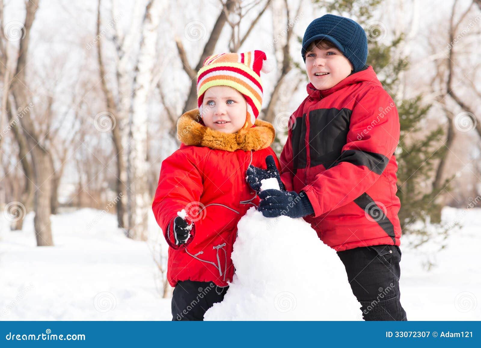 Παιχνίδι αγοριών και κοριτσιών με το χιόνι στο χειμερινό πάρκο