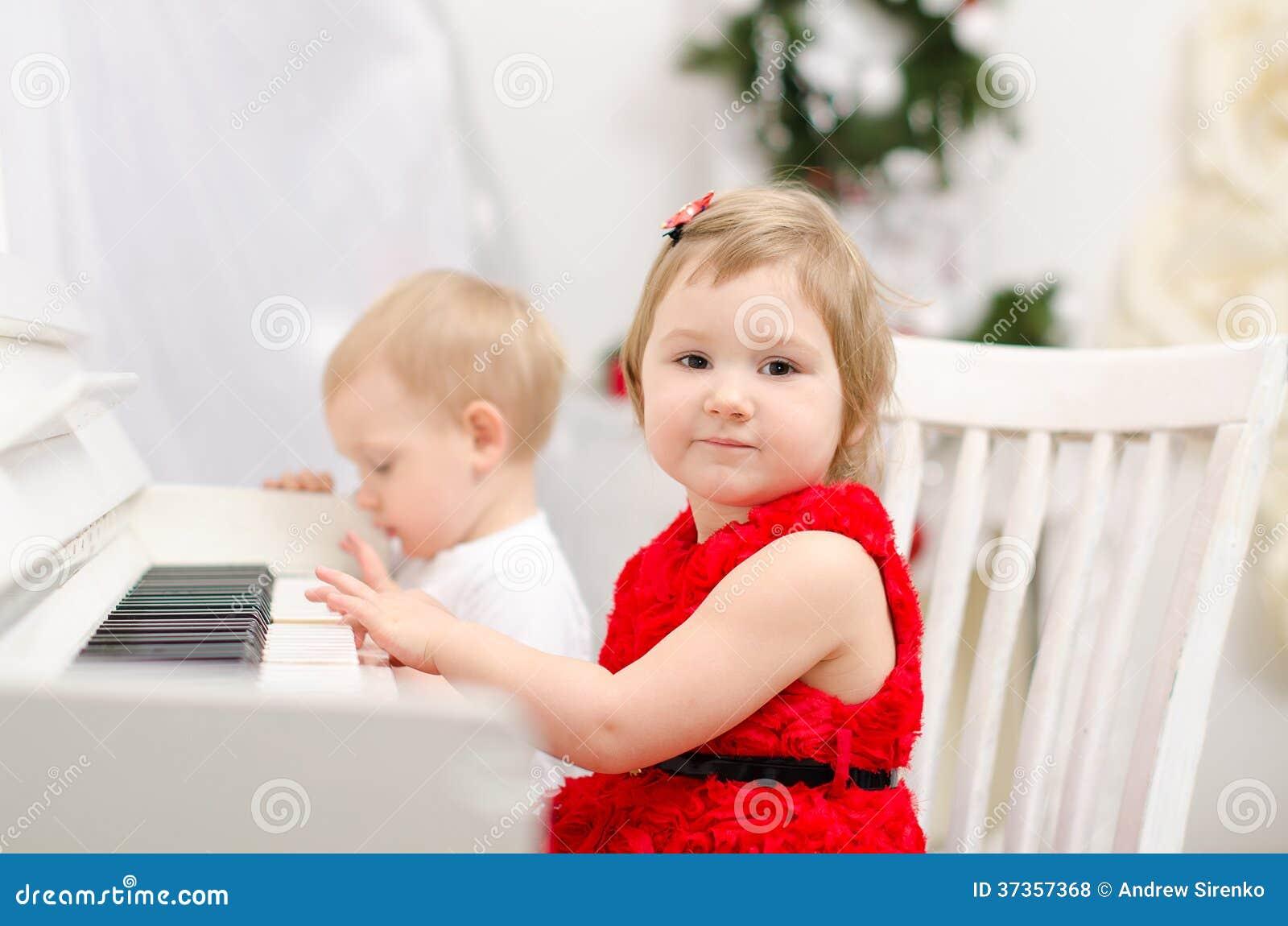 Παιχνίδι αγοριών και κοριτσιών στο άσπρο πιάνο