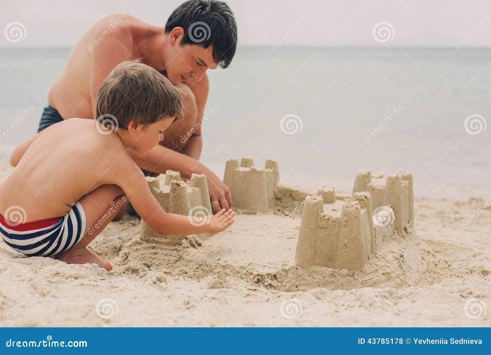 Παιδί και ο πατέρας του που χτίζουν sandcastle