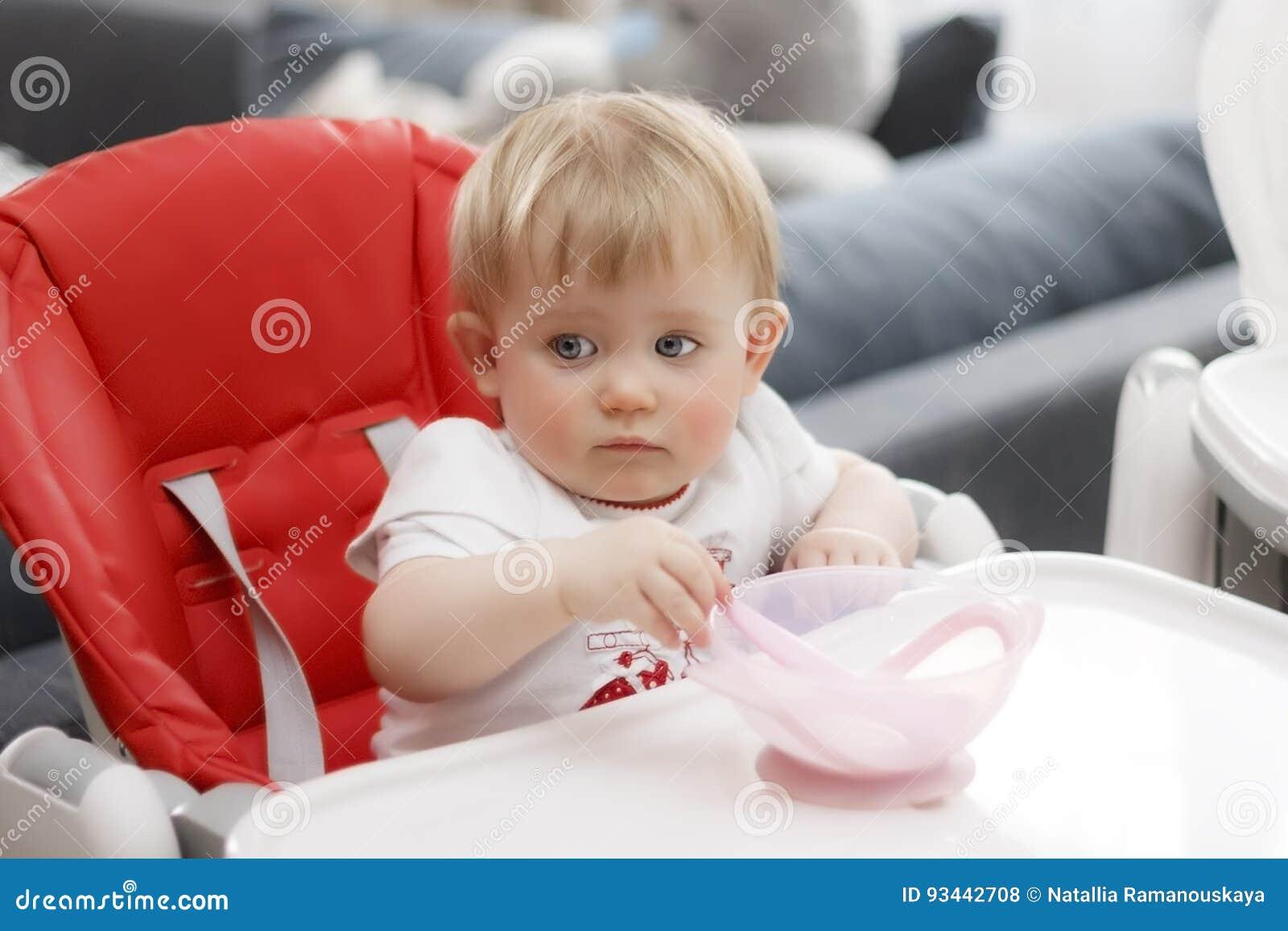 Παιδί με το ξανθό κουάκερ καθίσματος και κατανάλωσης μπλε ματιών