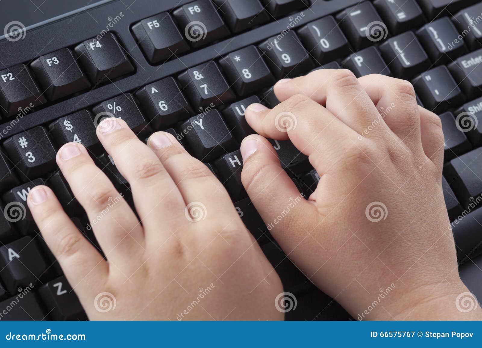 Παιδί που δακτυλογραφεί κάτι στο μαύρο πληκτρολόγιο υπολογιστών
