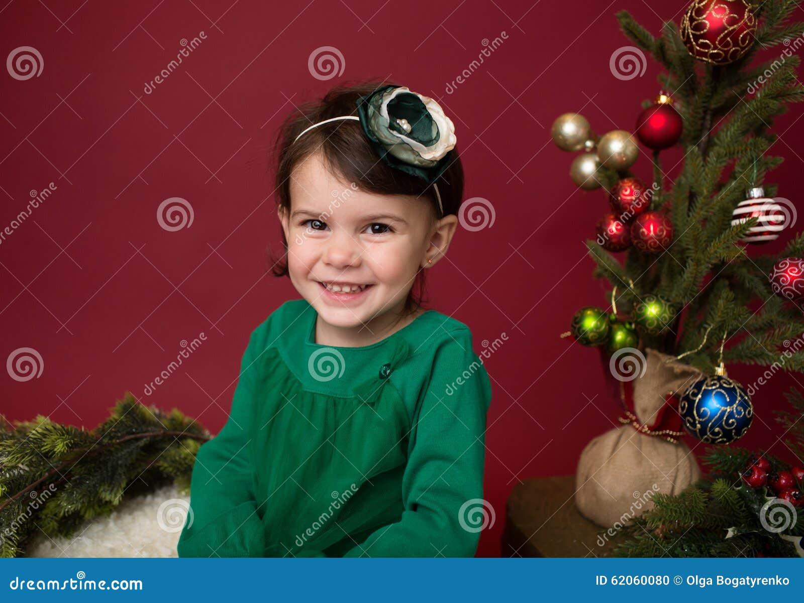 Παιδί Χριστουγέννων στο έλκηθρο ενάντια στο χριστουγεννιάτικο δέντρο με τις διακοσμήσεις