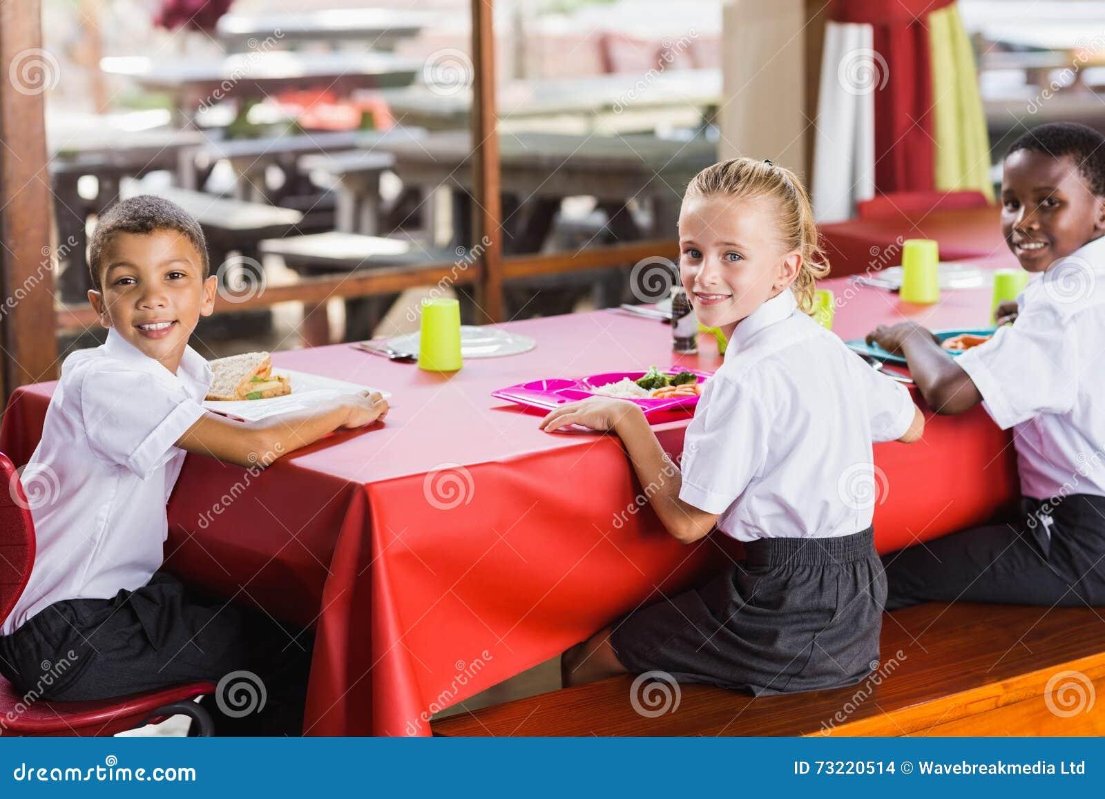 Παιδιά που έχουν το μεσημεριανό γεύμα κατά τη διάρκεια του χρόνου σπασιμάτων στη σχολική καφετέρια