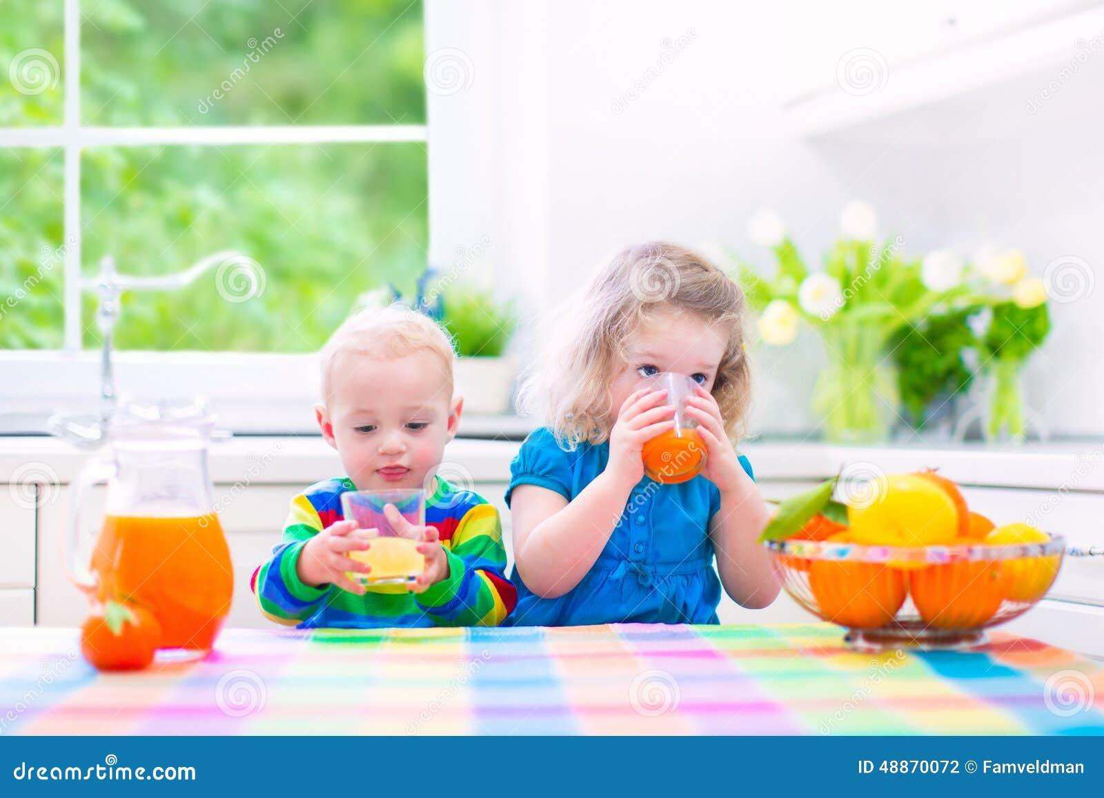 Παιδιά που πίνουν το χυμό από πορτοκάλι